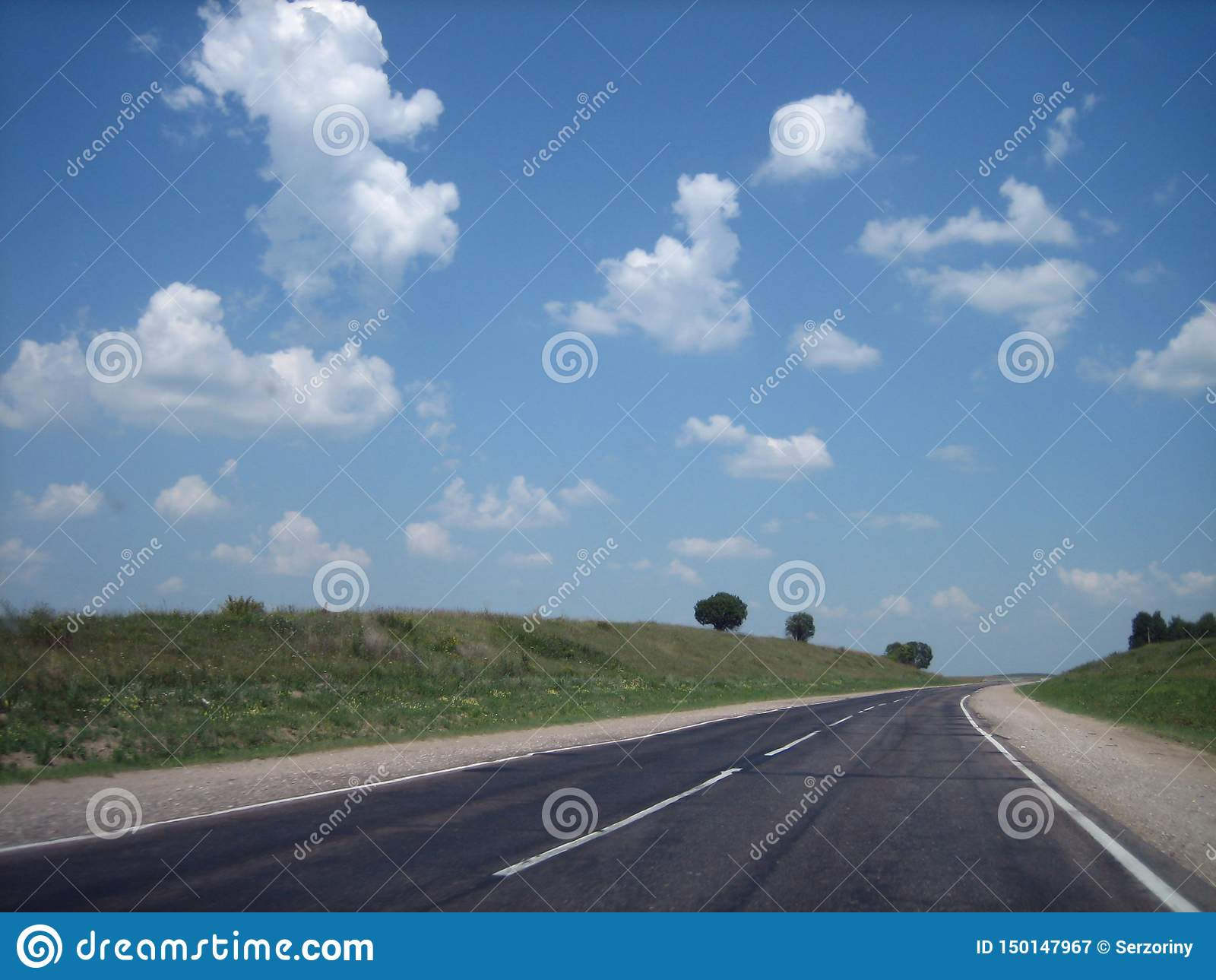 La carretera del coche en las grietas entra lejos la distancia en un día soleado brillante