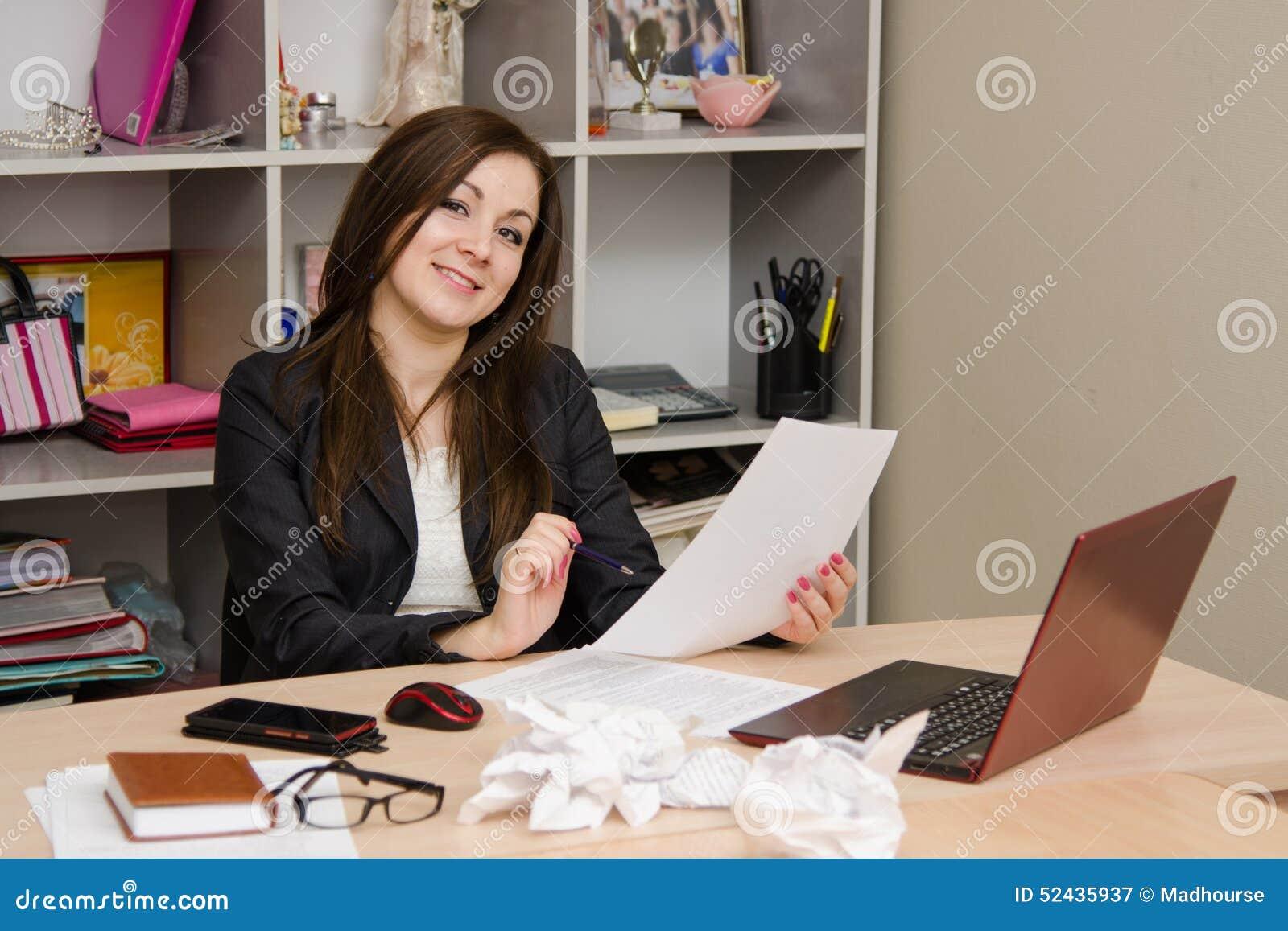 La carta della tenuta della ragazza di affari esamina la struttura e sorridere