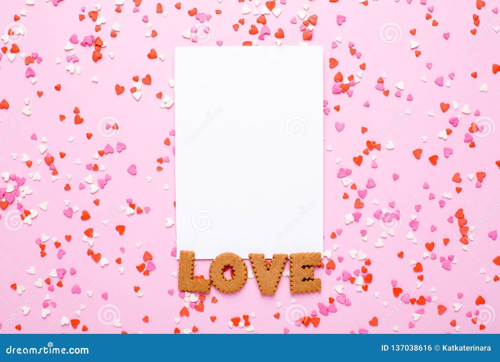 La carte actuelle avec des biscuits de lettres aiment et dentellent, les coeurs rouges sur le fond rose