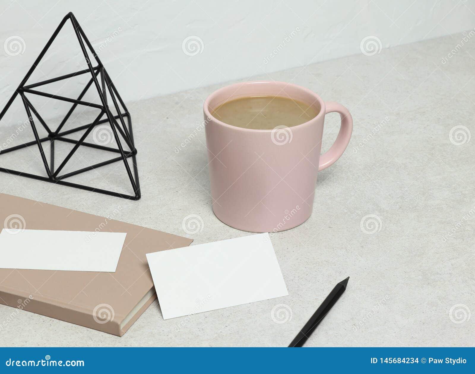 La carte de visite professionnelle de visite de maquette sur le granit avec le livre, le crayon et la statuette roses, tasse de c