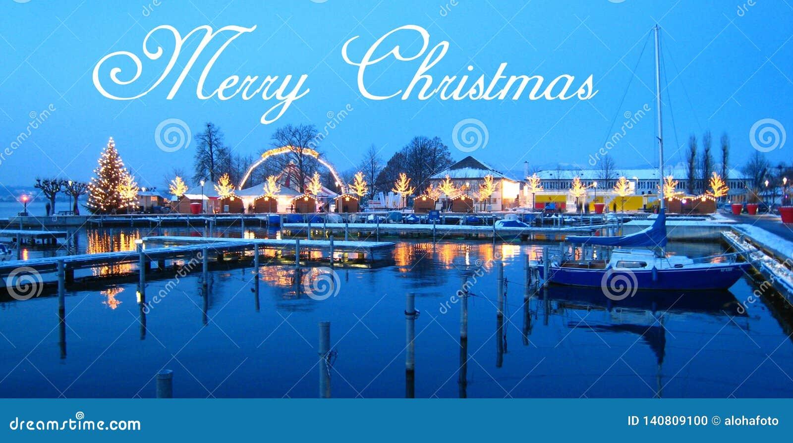 La carte postale avec un beau marché suisse de Noël de la Suisse sur le rivage de lac avec la neige a couvert des bateaux à l heu