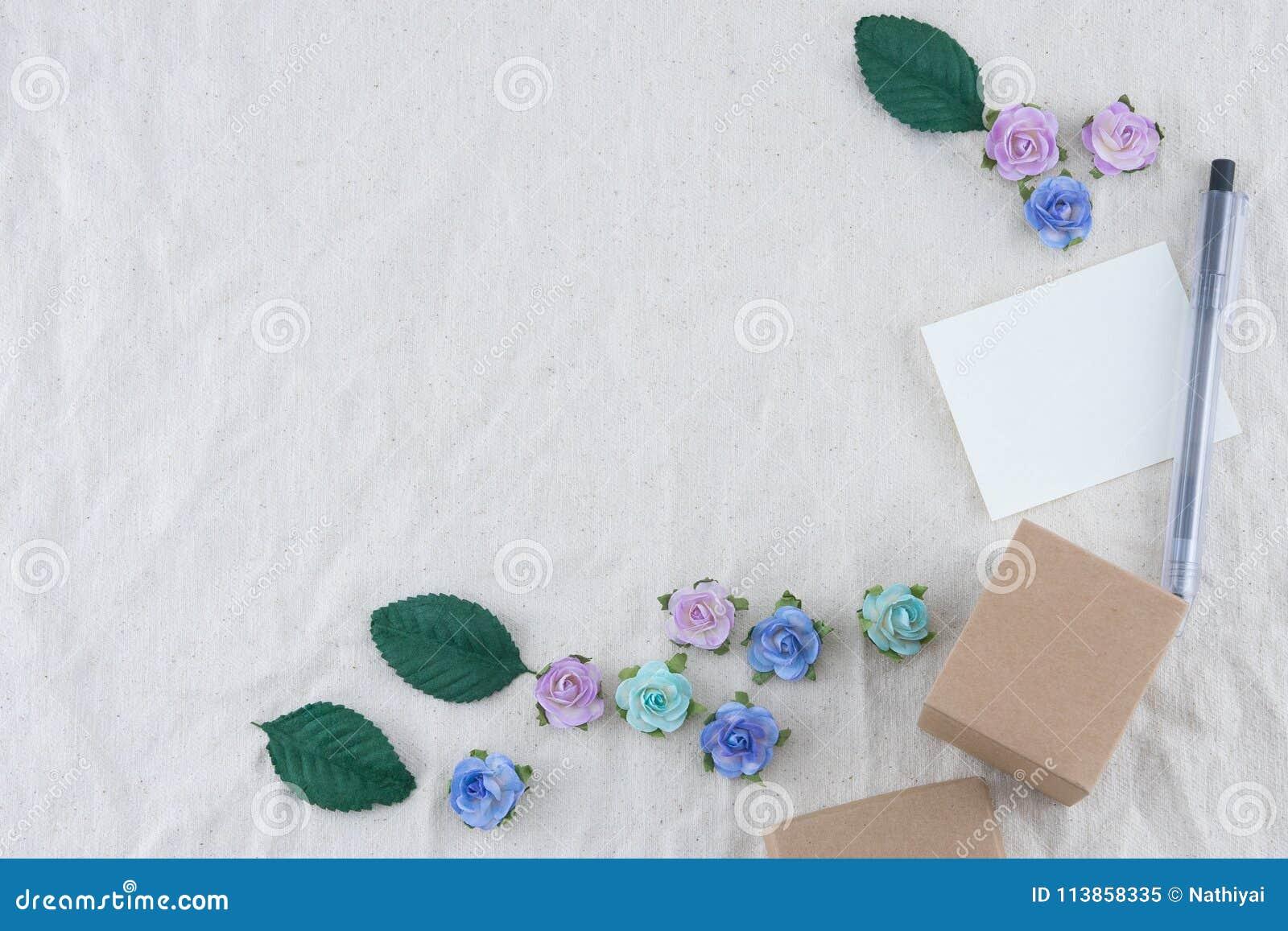La carte vierge blanche, le stylo et le boîte-cadeau brun décorent des fleurs de papier de ton bleu
