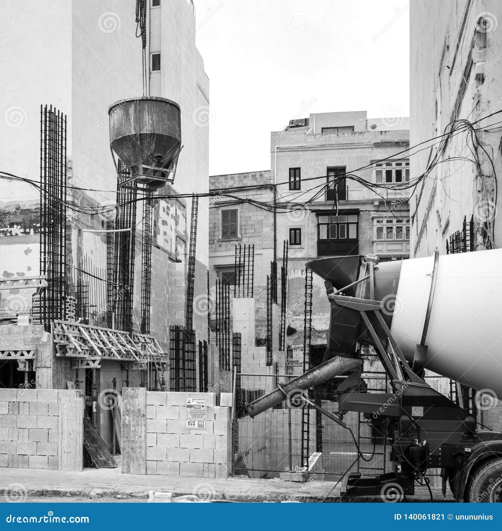 La casa bajo construcción está en curso con el equipo constructivo en el frente, St juliano, Malta