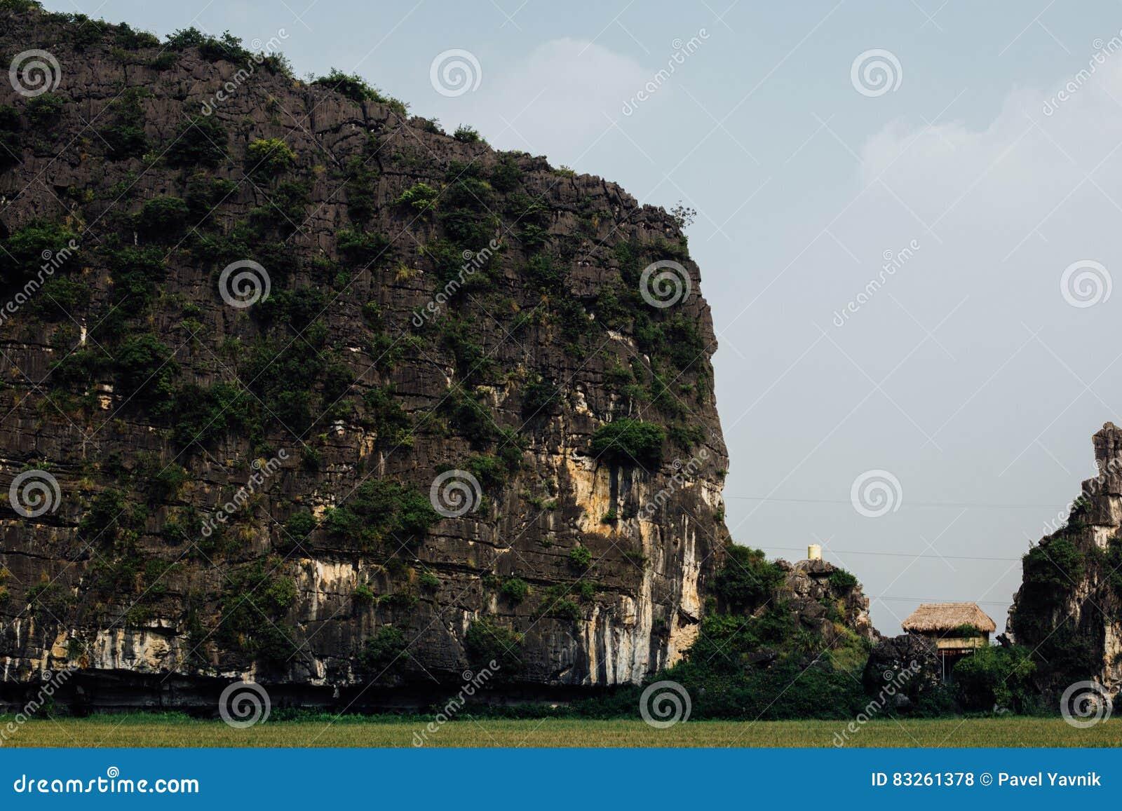 La casa de la paja dilapidó choza entre el acantilado y el soporte de la roca