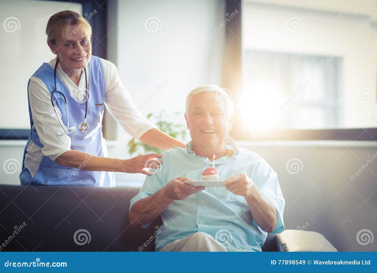 La celebrazione femminile senior di medico senior equipaggia il compleanno in ospedale