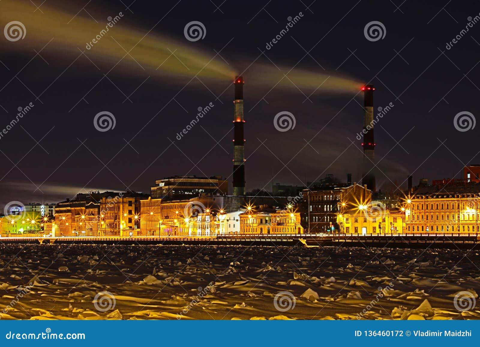 La central térmica de la noche del invierno en el terraplén del río de Neva en St Petersburg