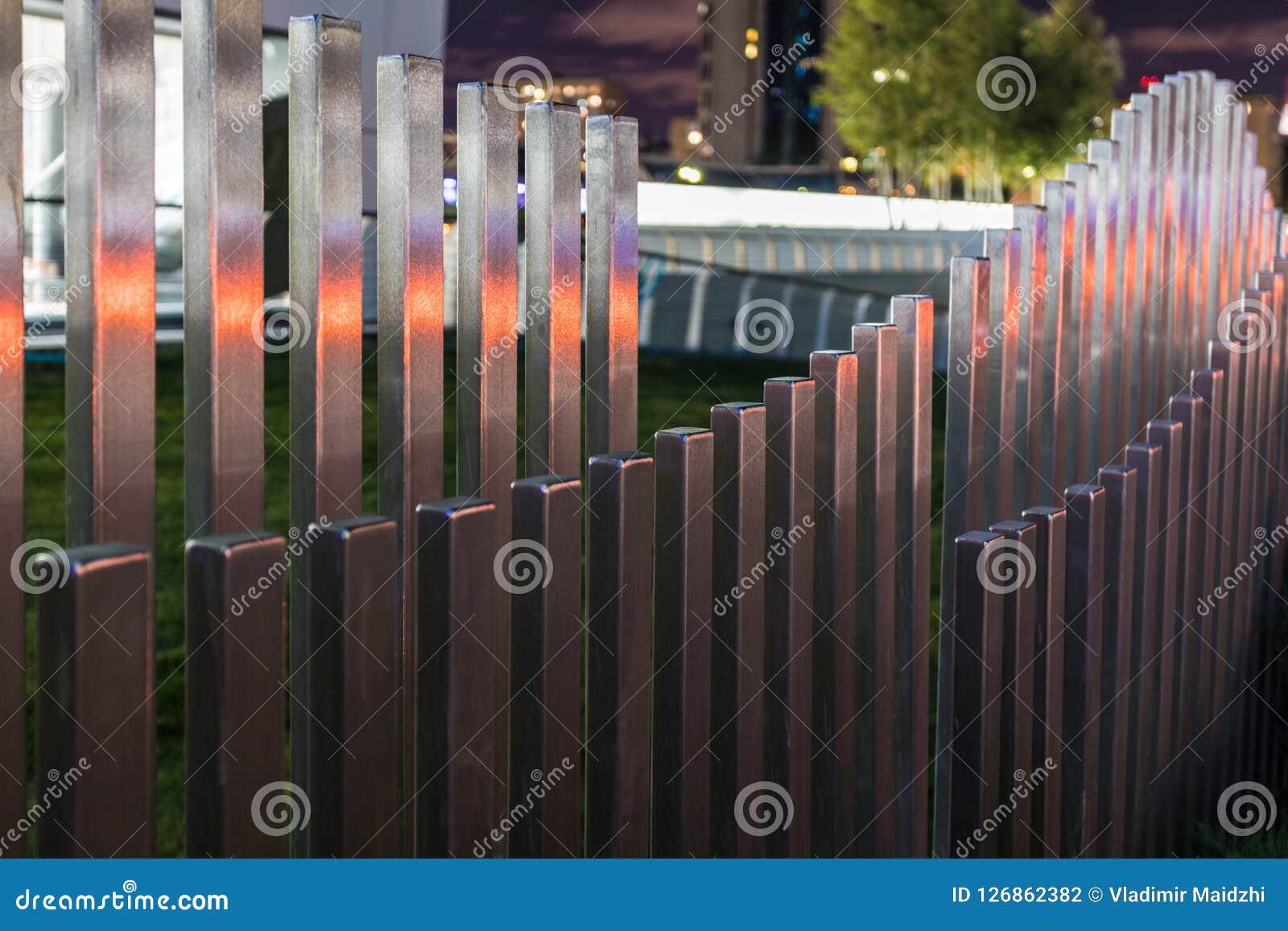 La cerca de madera ondulada cerca del camino en los colores de los semáforos de coche