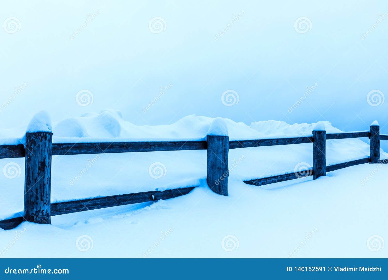 La cerca o el seto y los montones de la nieve en el campo o en el pueblo en el día de invierno frío