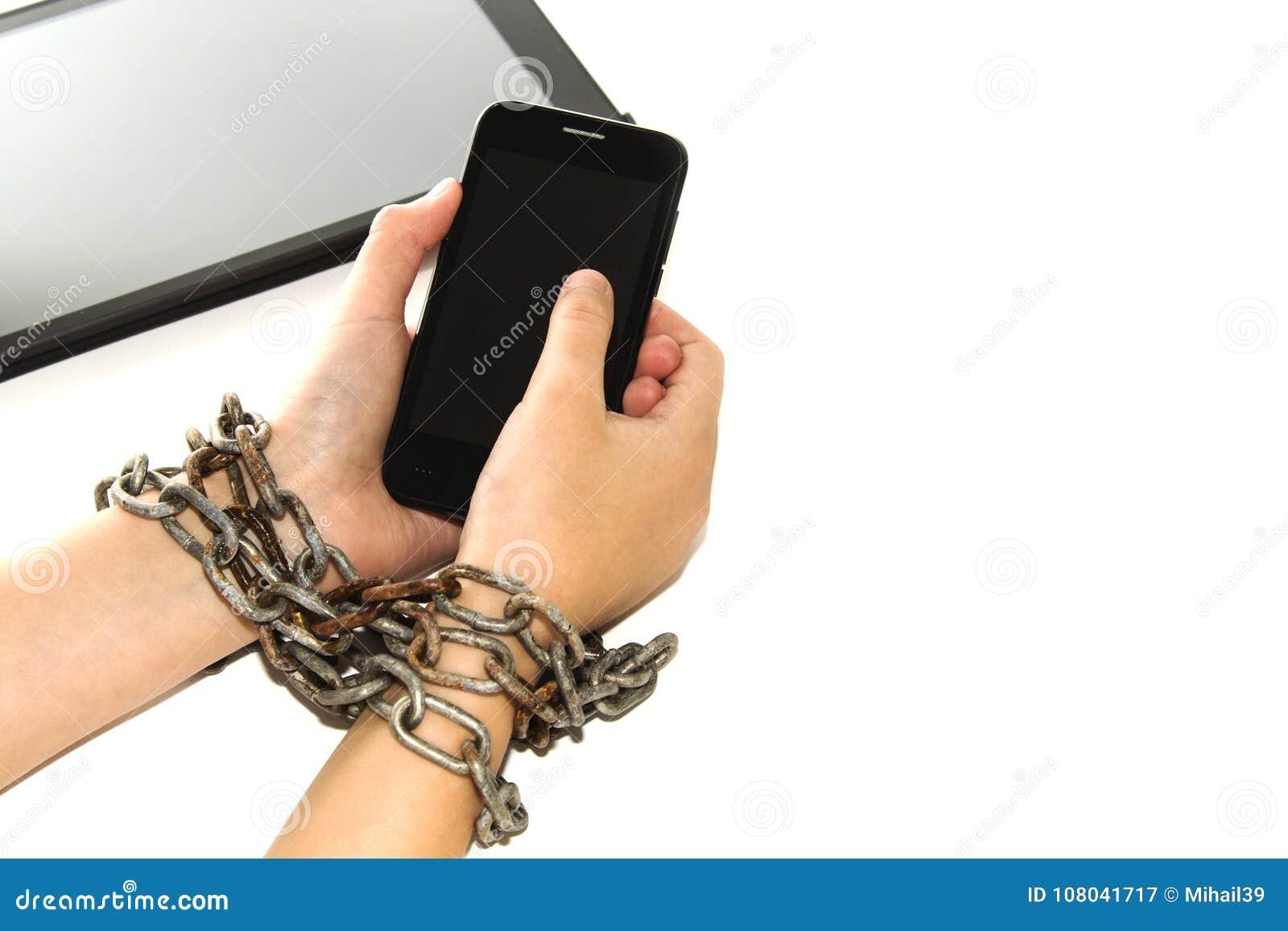 La chaîne de fer attache ensemble les mains et le smartphone - concept de dépendance de téléphone portable