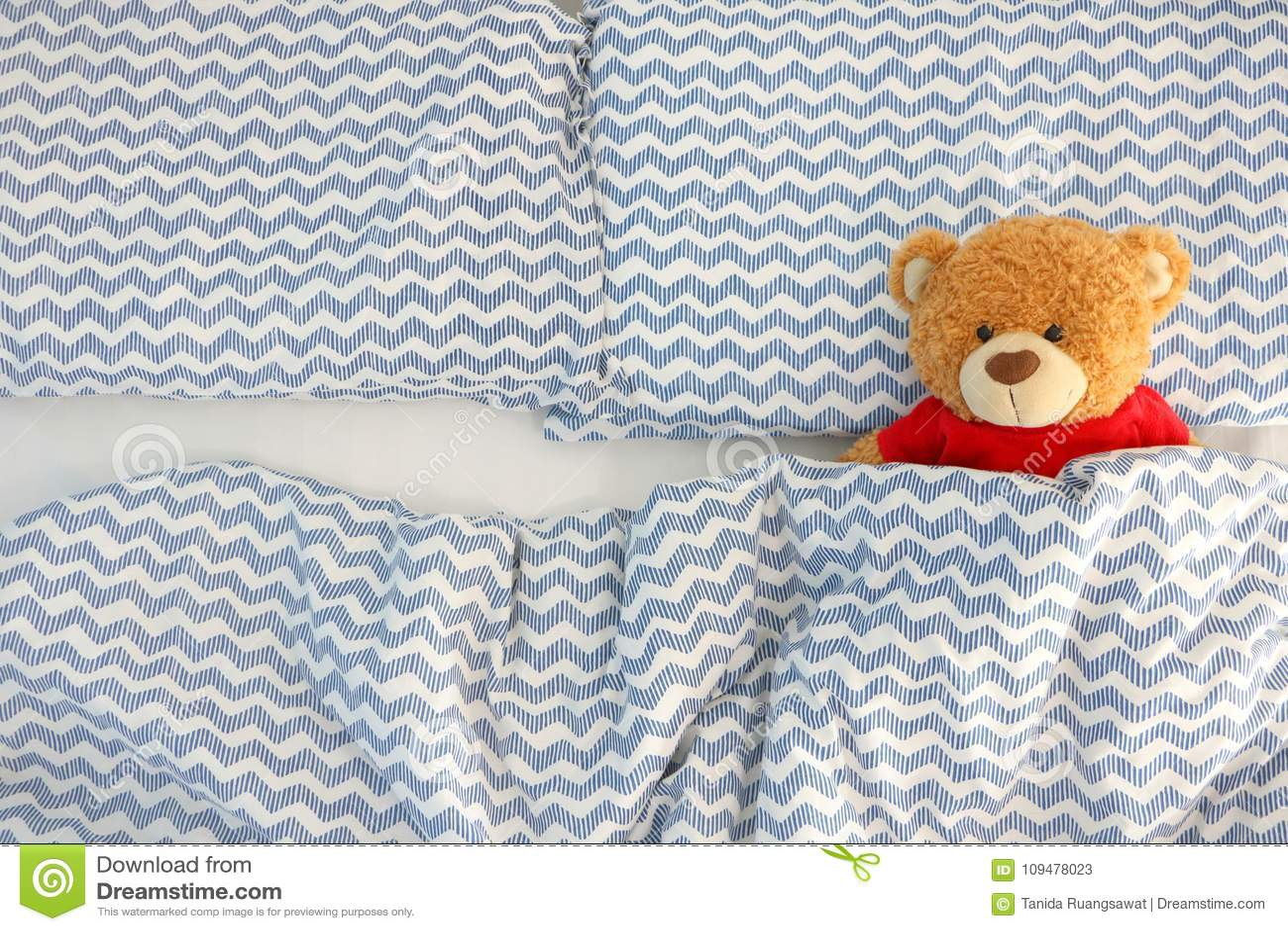 La chemise rouge d ours brun d usage simple de poupée dormant sur le lit ont l espace du côté gauche Concept attendant quelqu un