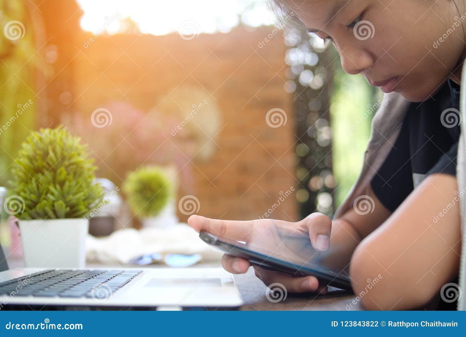 La chica joven del primer utilizó el teléfono móvil, fondo borroso