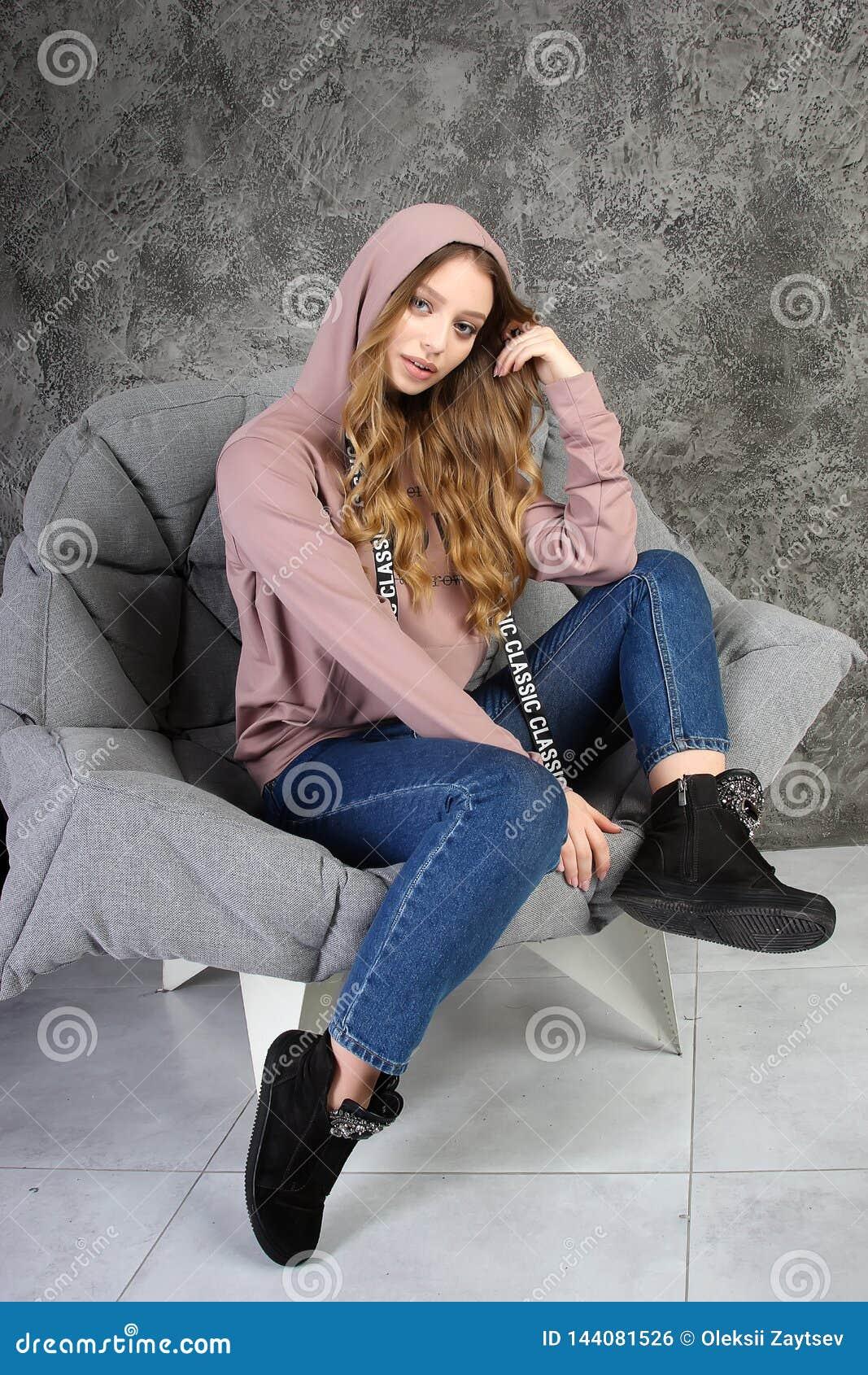 La chica joven en un chándal se sienta en un interior elegante