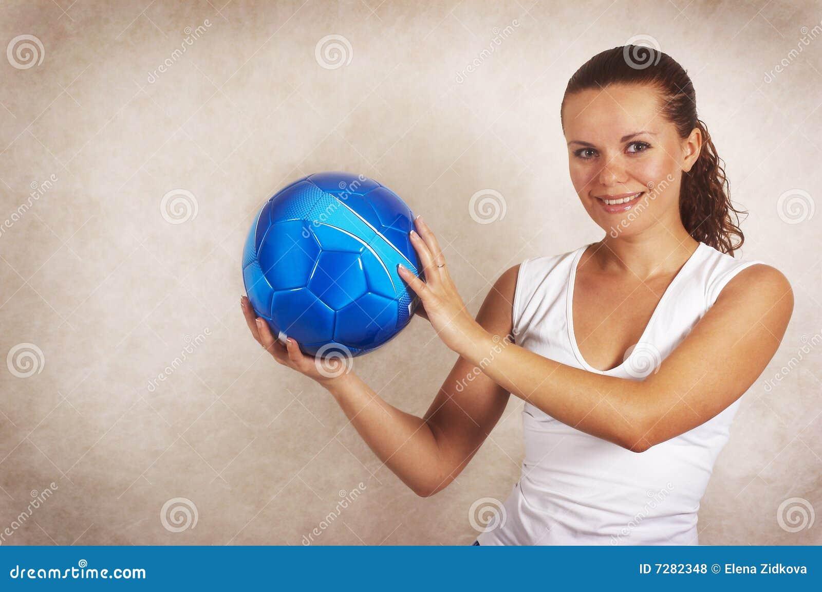 La chica joven hermosa con la bola sonríe (el primer)