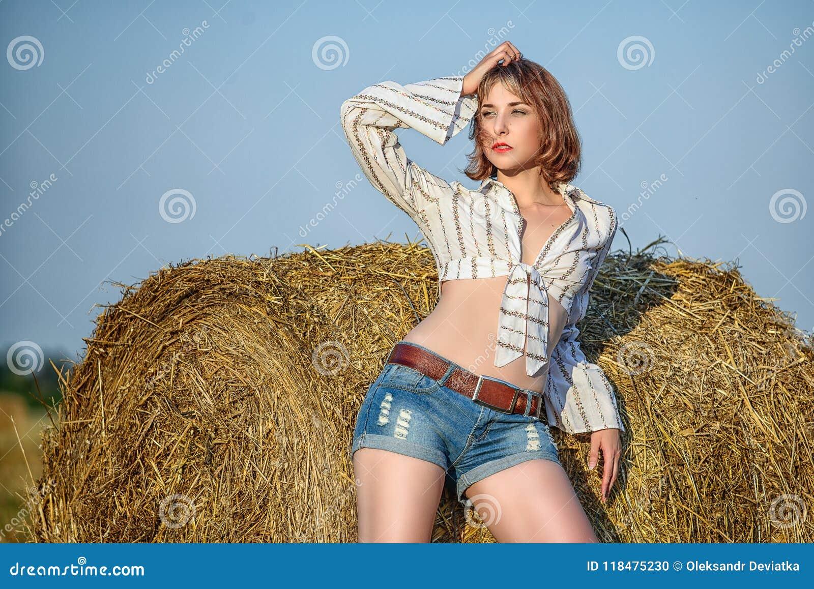 La chica joven hermosa con las piernas finas largas y el vientre desnudo en un dril de algodón pone en cortocircuito y camisa en