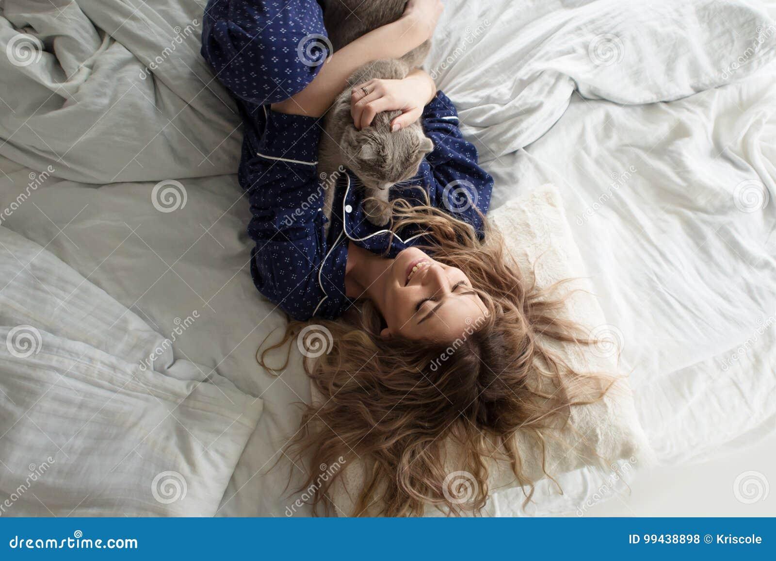 a5c23db2a7 La Chica Joven Hermosa En Pijamas Abraza Su Gato Que Miente En La ...