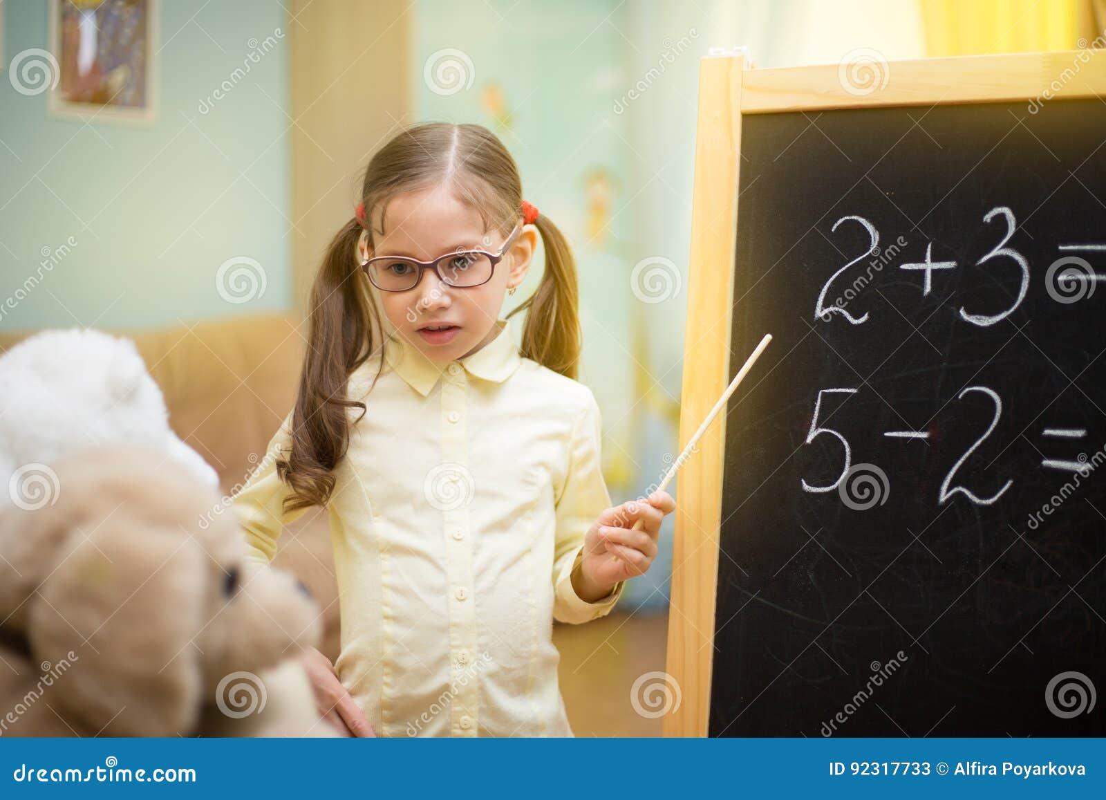 La chica joven hermosa está enseñando a los juguetes en casa en la pizarra Educación casera preescolar