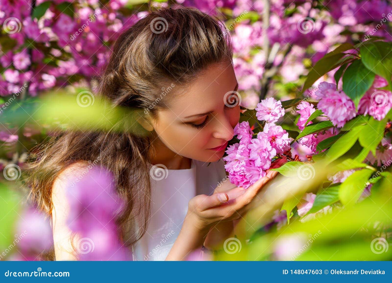 La chica joven hermosa huele las flores rosadas, Sakura floreciente en jard?n de la primavera