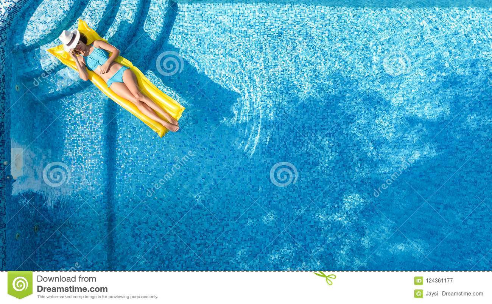 La chica joven hermosa que se relaja en la piscina, nadadas en el colchón inflable y se divierte en agua el las vacaciones de fam