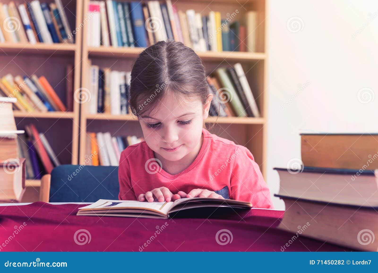 La chica joven lee un libro en biblioteca