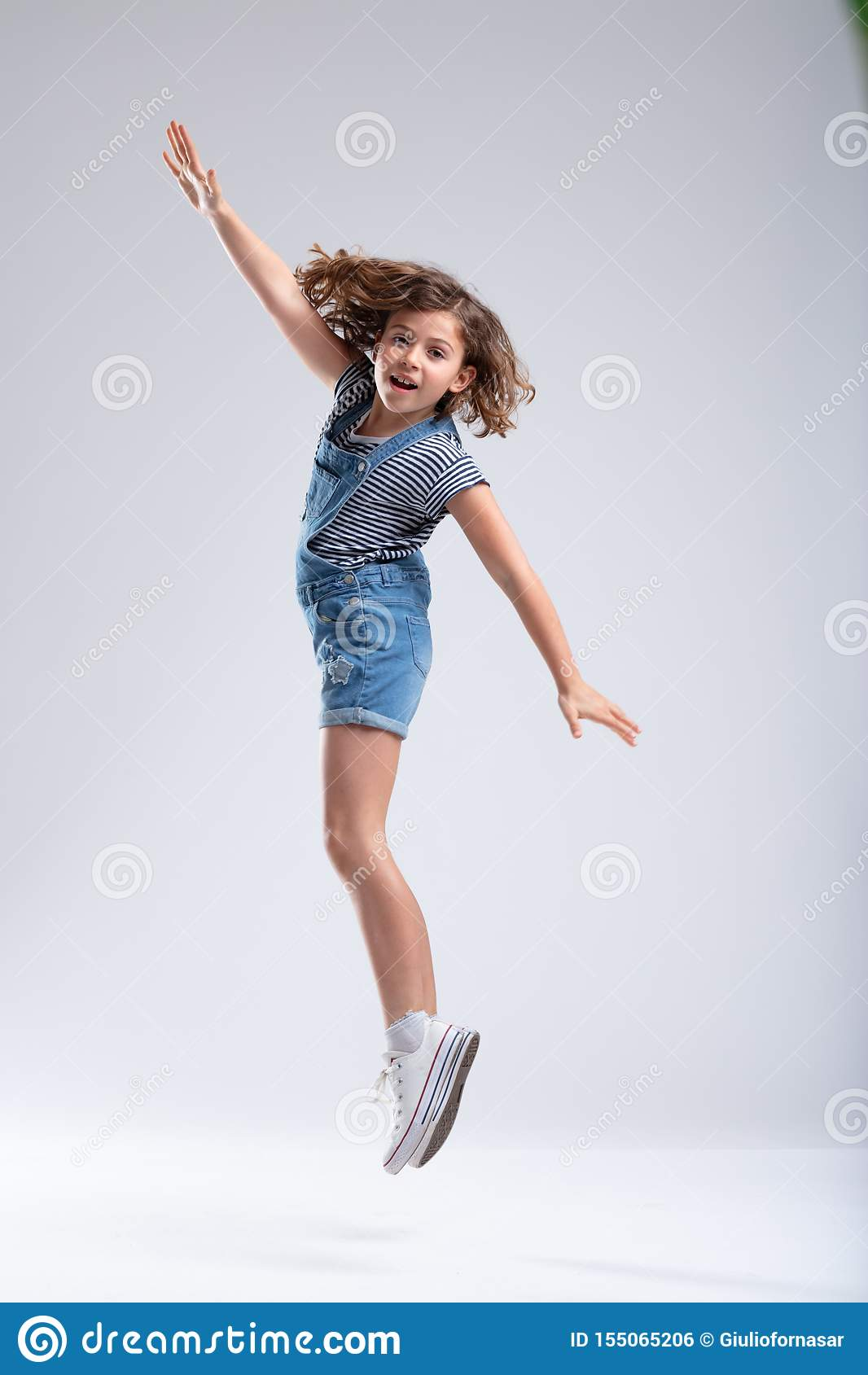 La chica joven que salta en el aire con los brazos extendidos