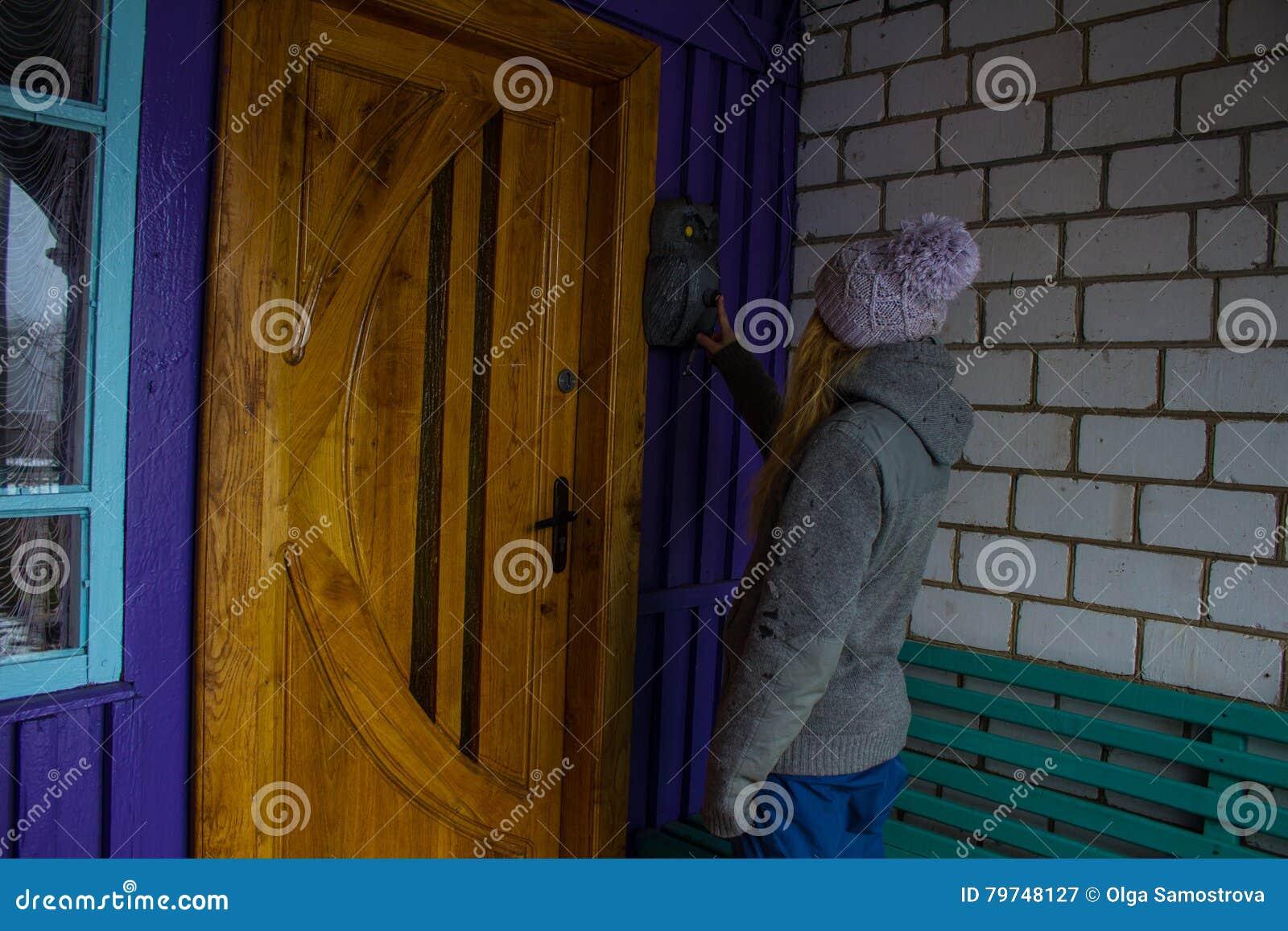 La chica joven suena la puerta de la casa en el invierno Fondo