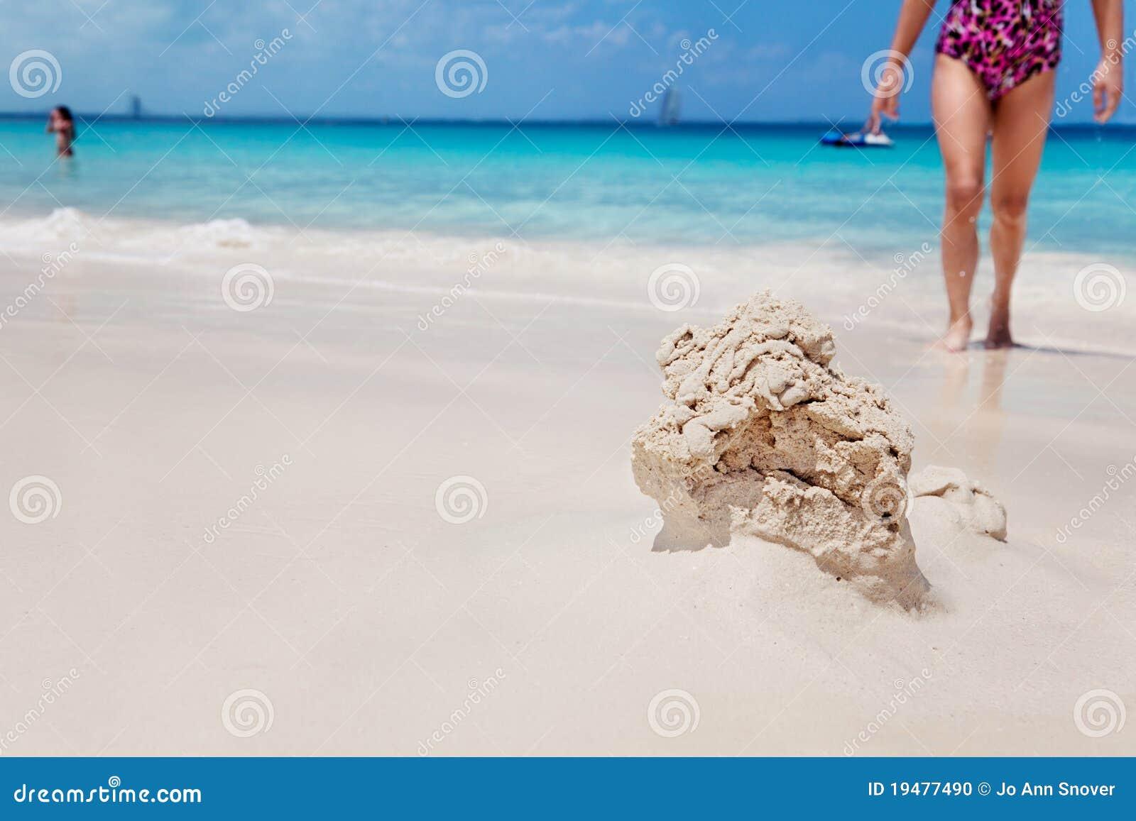 La chica joven vuelve al castillo de arena que desmenuza
