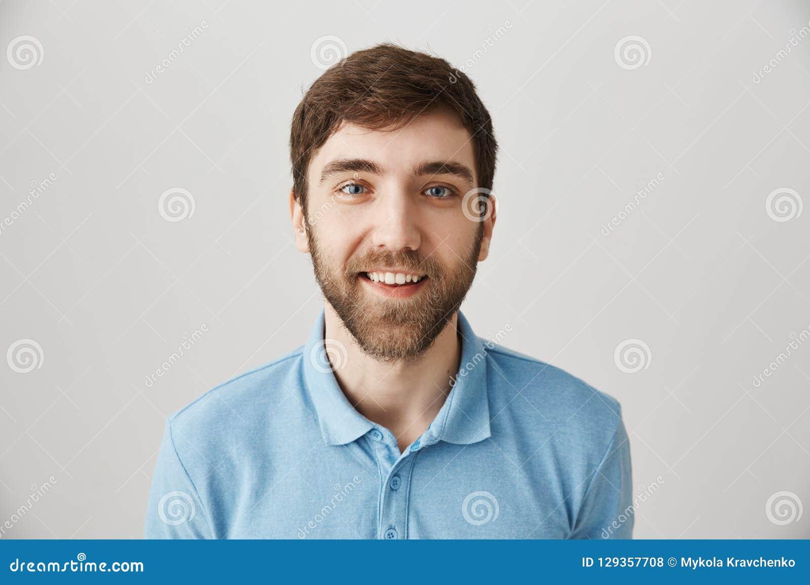 La cintura-para arriba tiró de individuo barbudo adulto emotivo divertido en polo azul, haciendo caras, sonriendo ampliamente y e