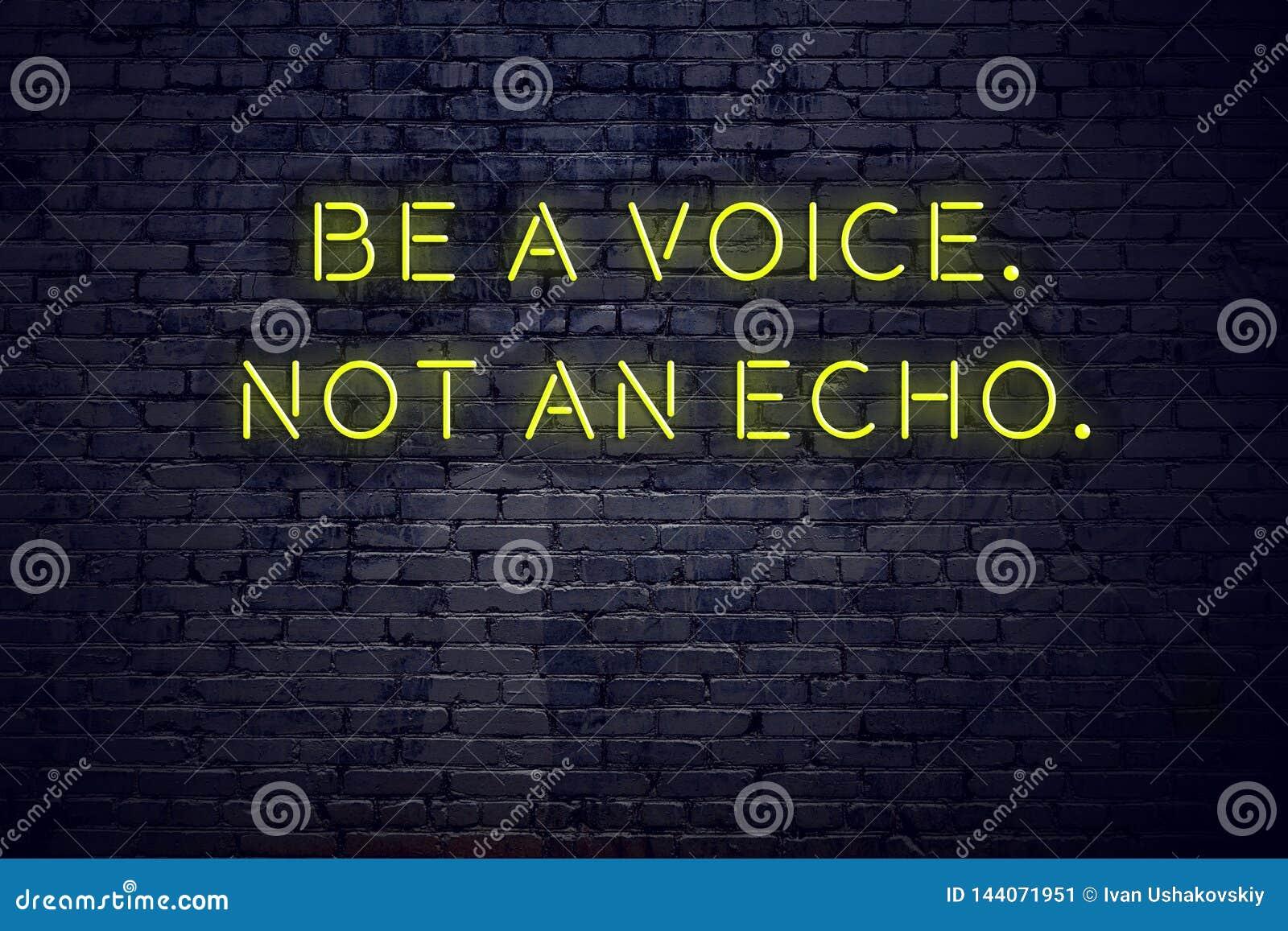 La cita inspiradora positiva en señal de neón contra la pared de ladrillo sea una voz no un eco