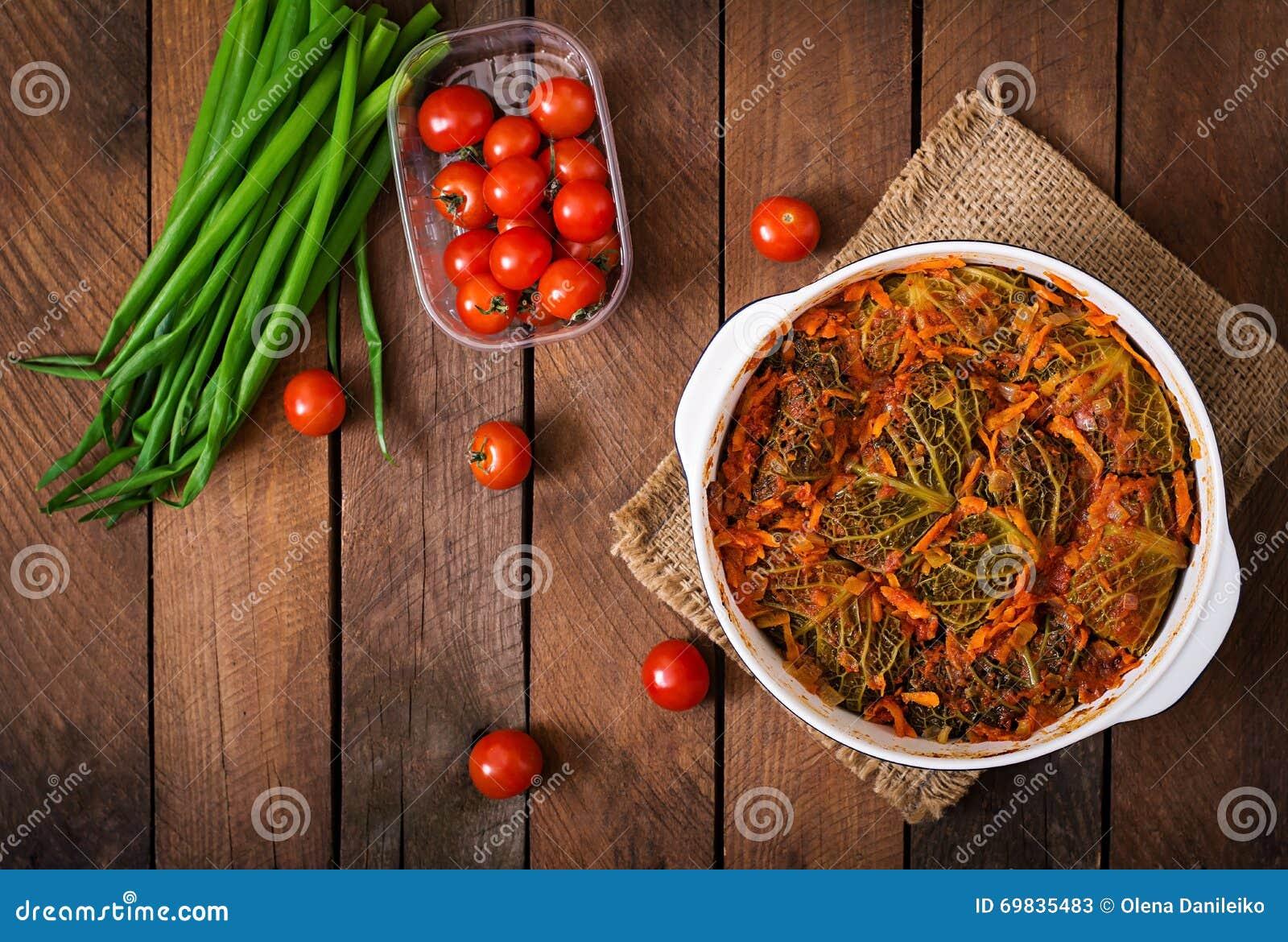 La col de col rizada rellena rueda en salsa de tomate