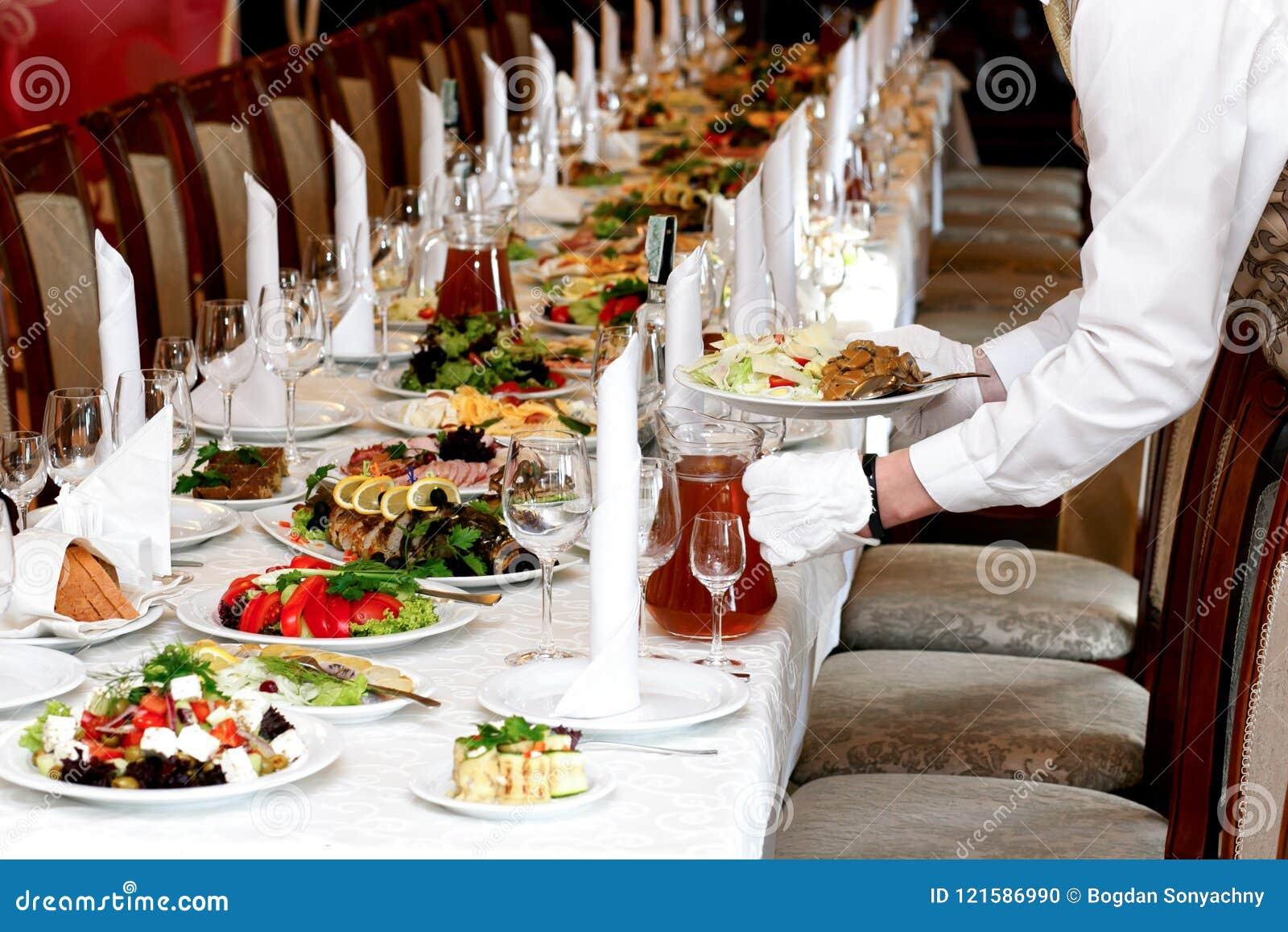 La comida de la porción del camarero en la tabla de lujo fijó en la recepción nupcial, Ca