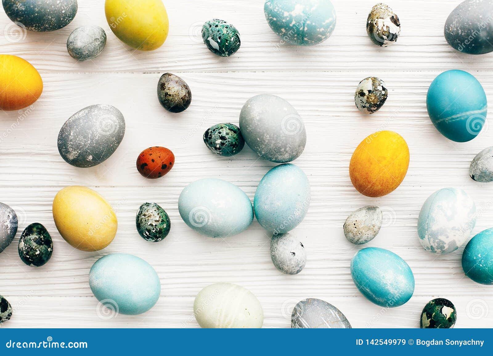 La composition élégante en oeufs de pâques, s étendent à plat sur le fond en bois blanc Oeufs de pâques colorés modernes peints a