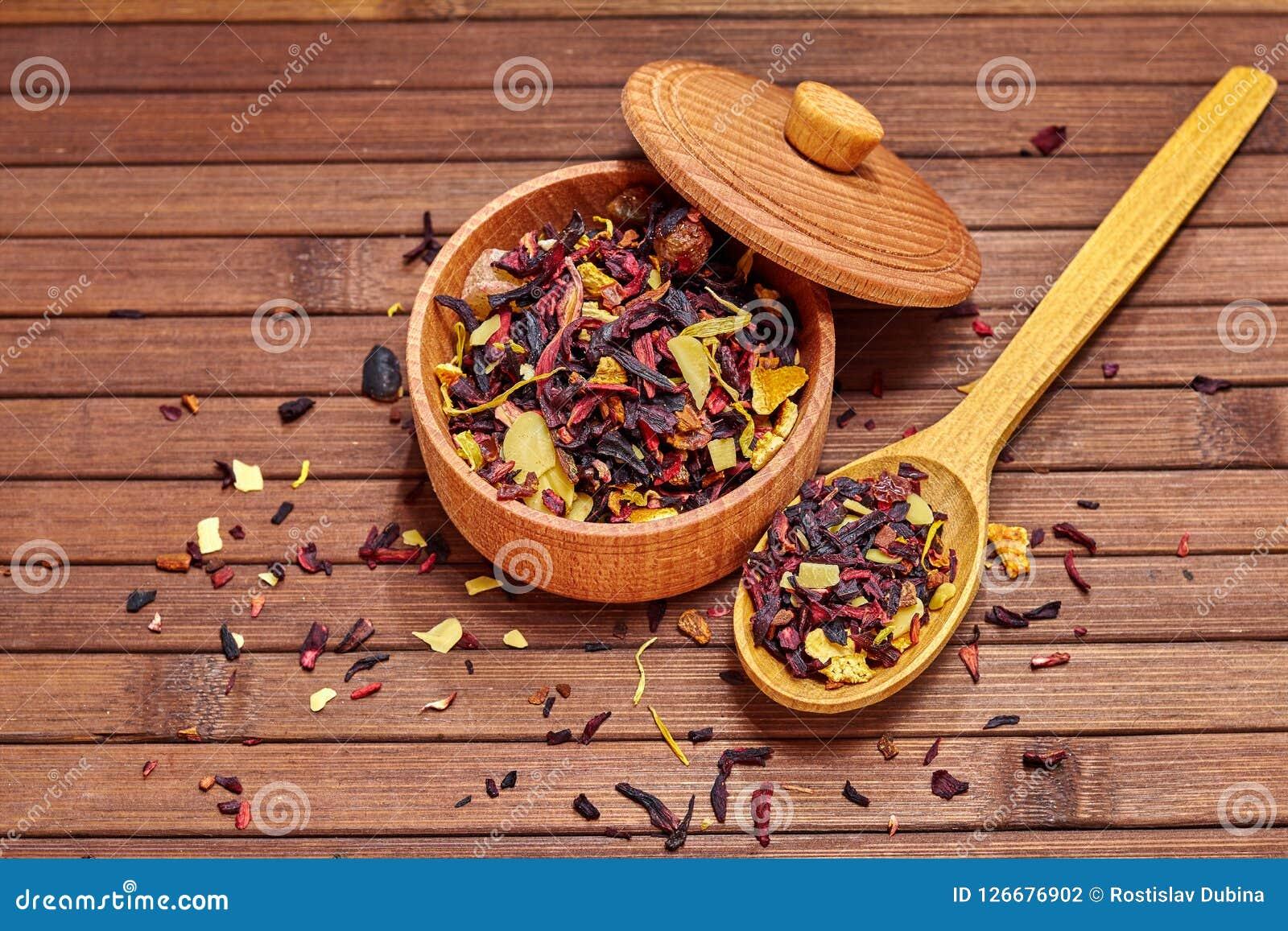 La composizione di tè naturale con foglie di è aumentato Macro foto dei petali del tè in un bordo di legno Il tè con i petali del
