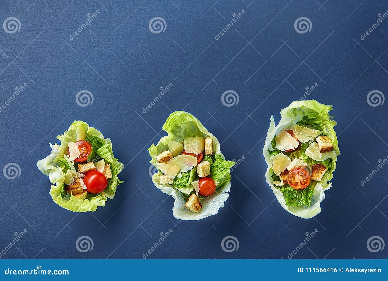 La composizione squisita di vista superiore di insalata sana fresca è servito in foglie della lattuga su fondo scuro