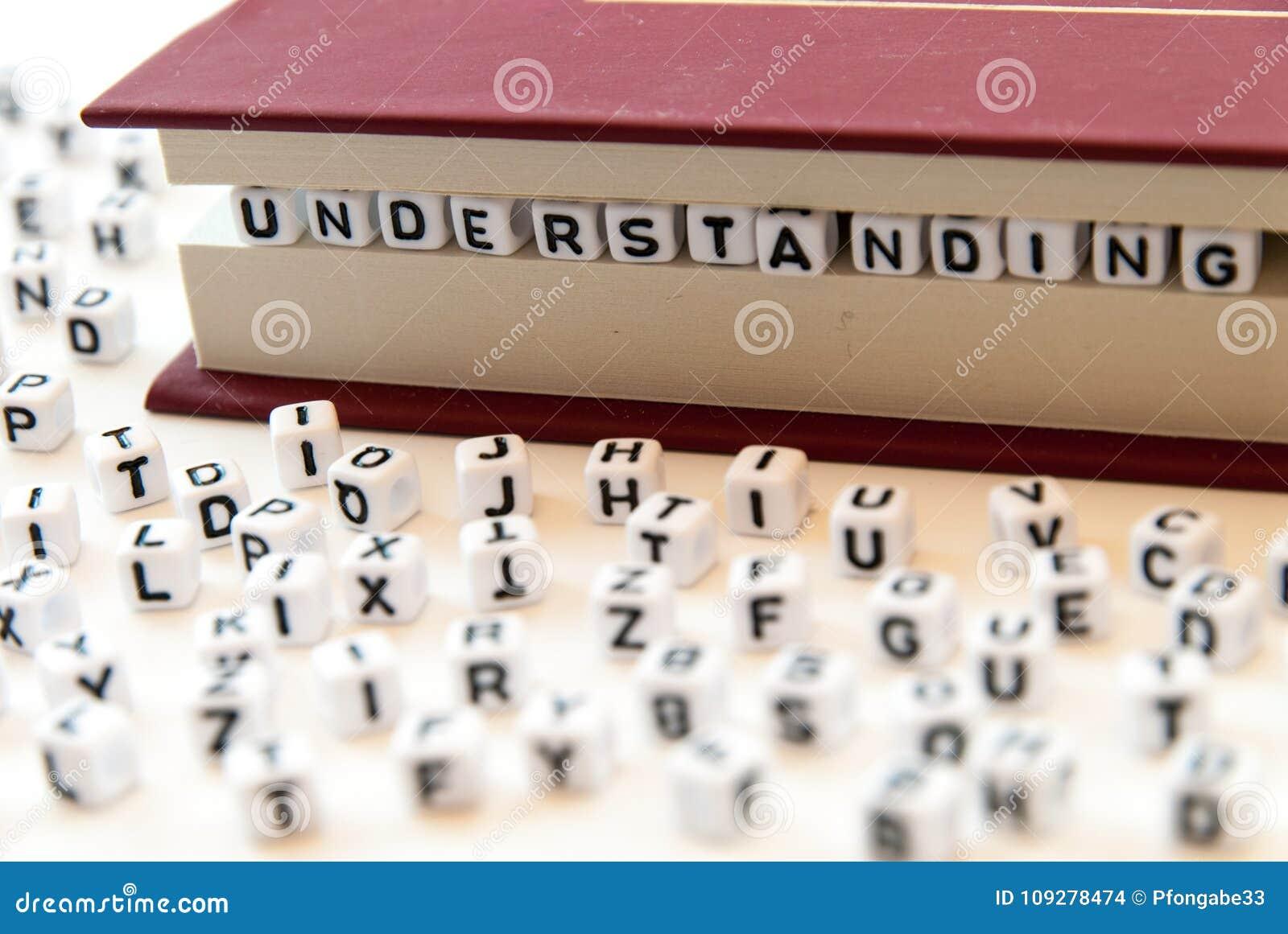La comprensione di parola scritta con le lettere fra un libro impagina il fondo bianco con le lettere sparse intorno al concetto