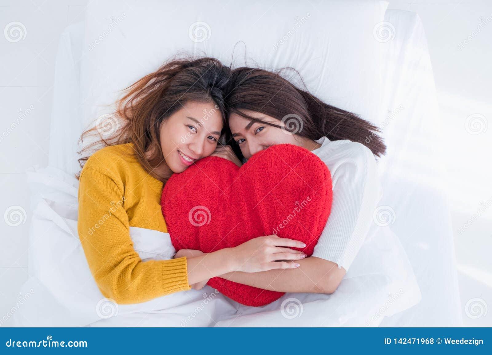 La configuration lesbienne de couples de l Asie LGBT sur l arc-en-ciel de lit et d étreinte colorent la forme de coeur d oreiller