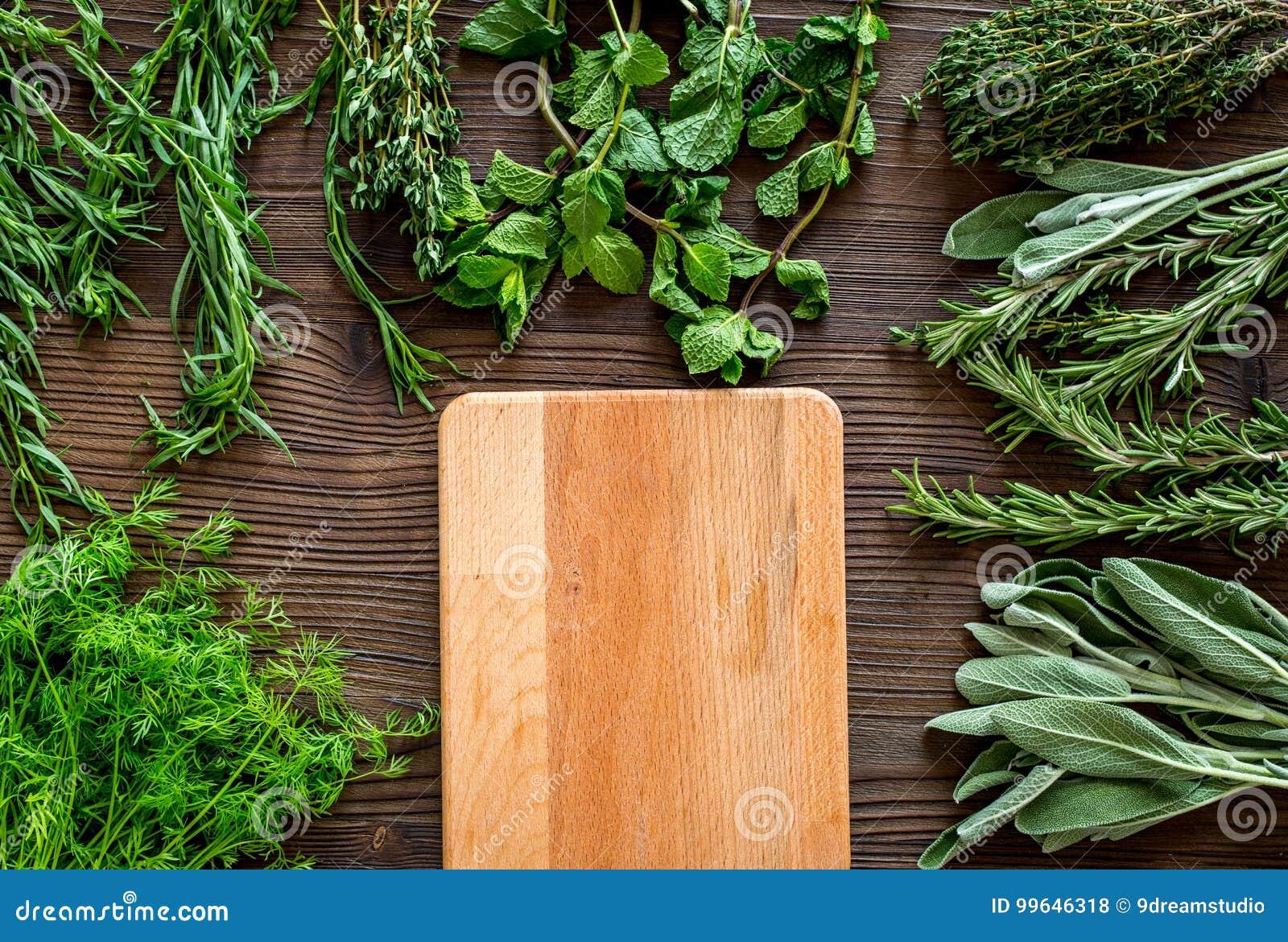 La configuration plate avec les herbes et la verdure fraîches pour sécher et faire des épices a placé sur la maquette en bois de