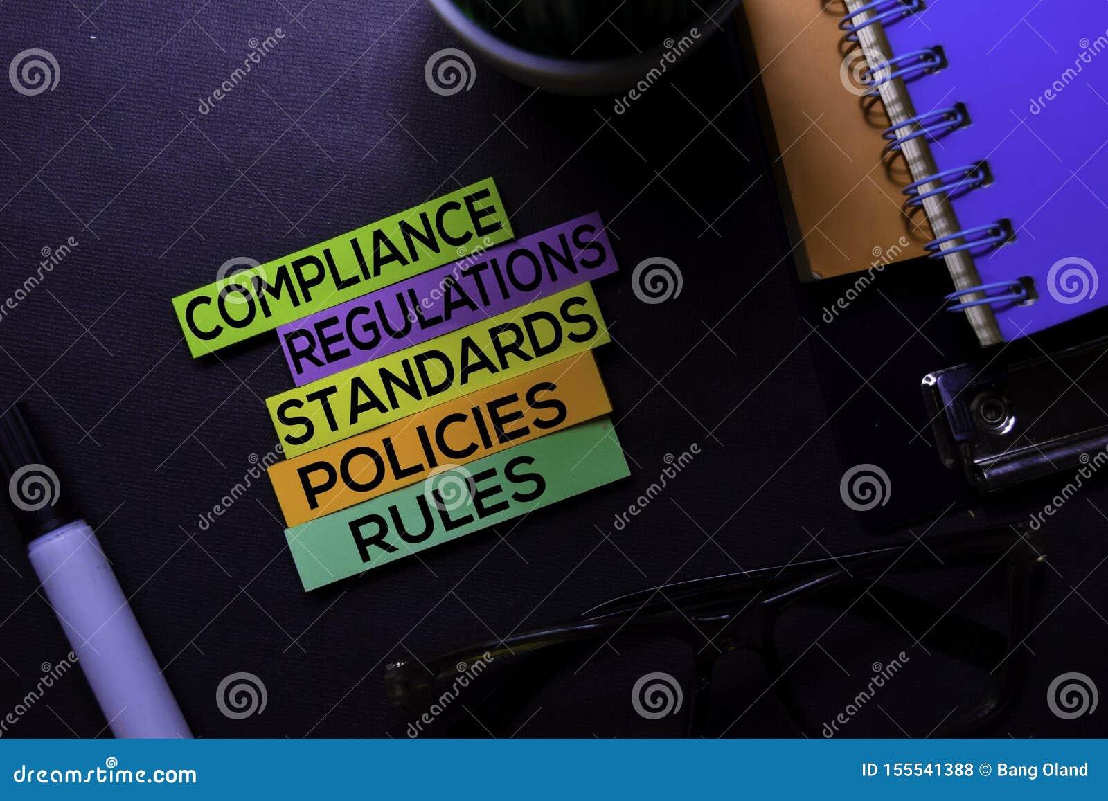 La conformidad, regulaciones, Strandards, políticas, reglas manda un SMS en las notas pegajosas aisladas en el escritorio negro C