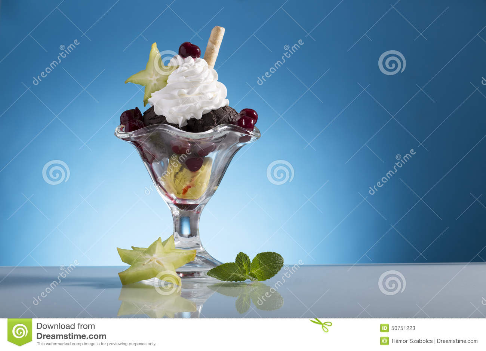 La coppa gelato variopinta della ciliegia con crema wipping e la carambola decorano