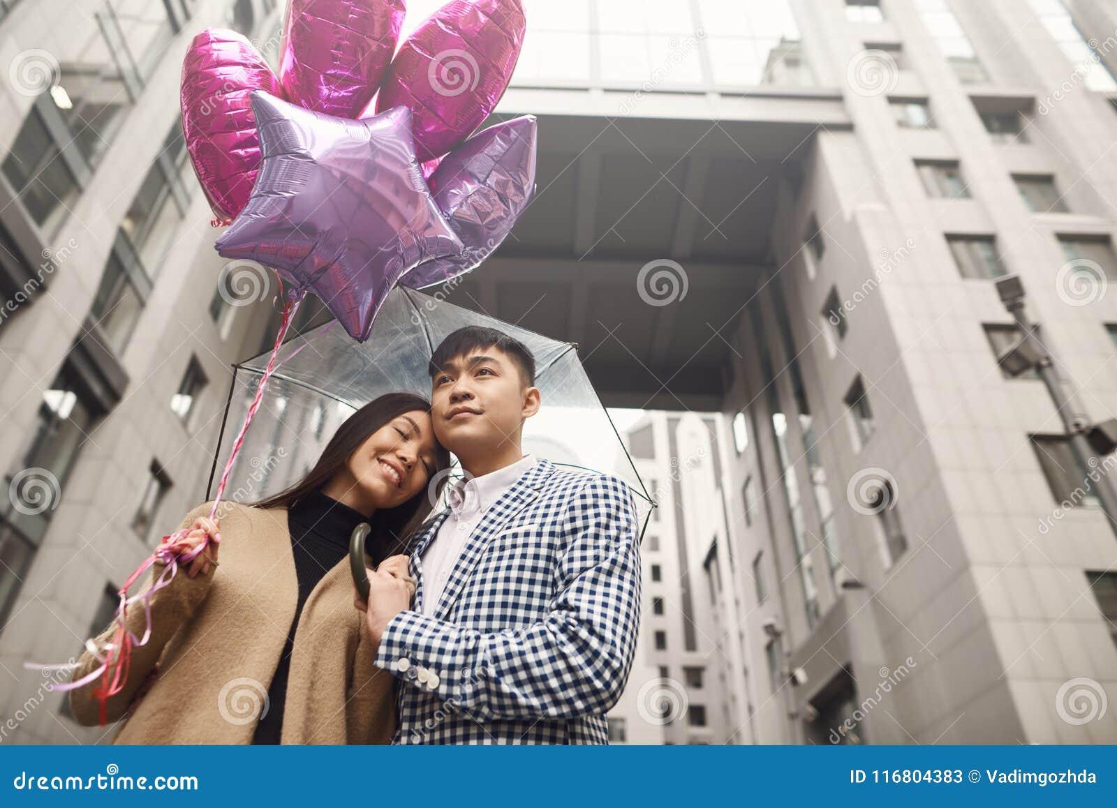La coppia nell amore sotto l ombrello con i palloni passeggia lungo il viale