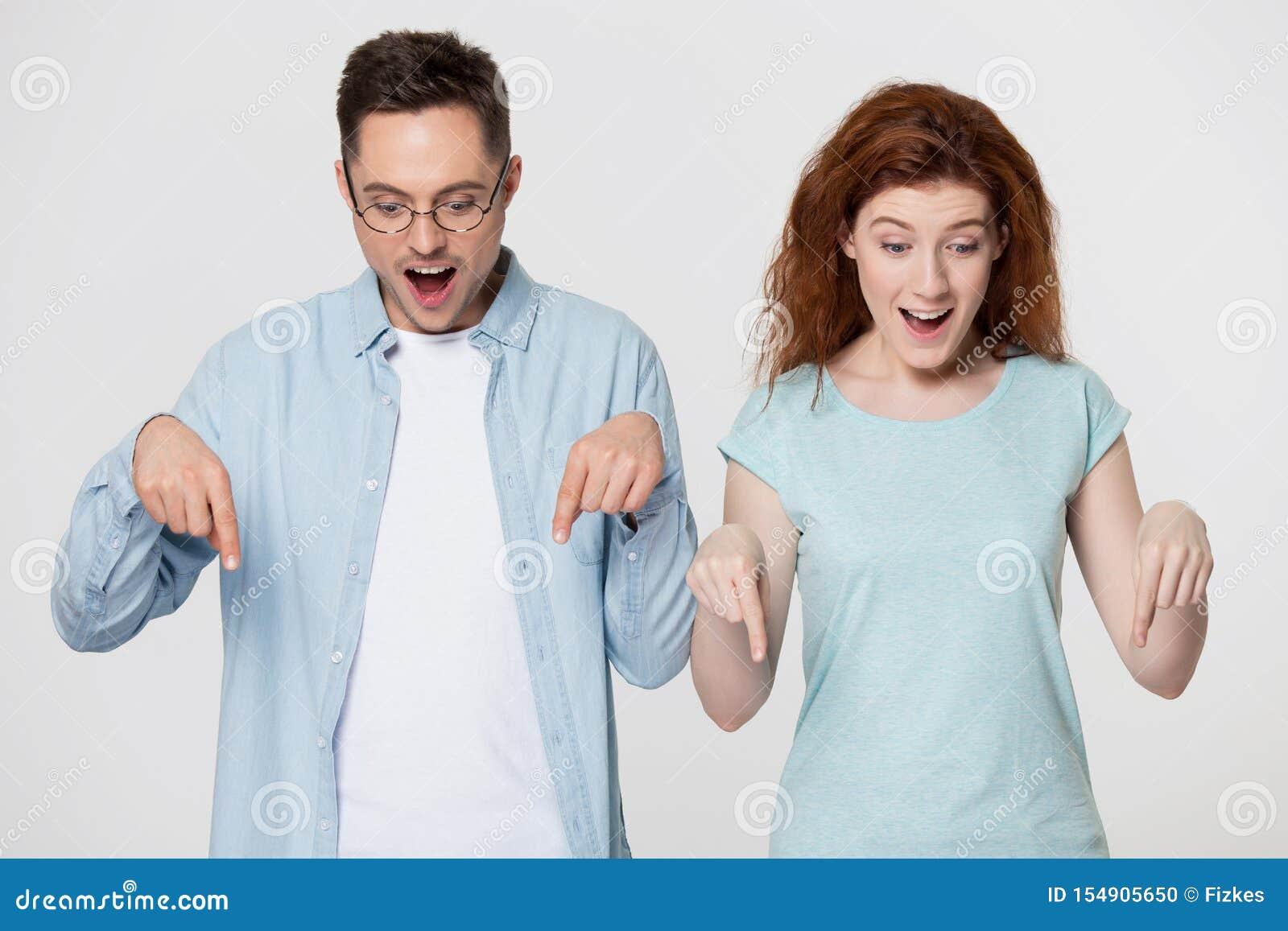 La coppia positiva millenaria ritiene stupita indicando le dita giù l immagine dello studio