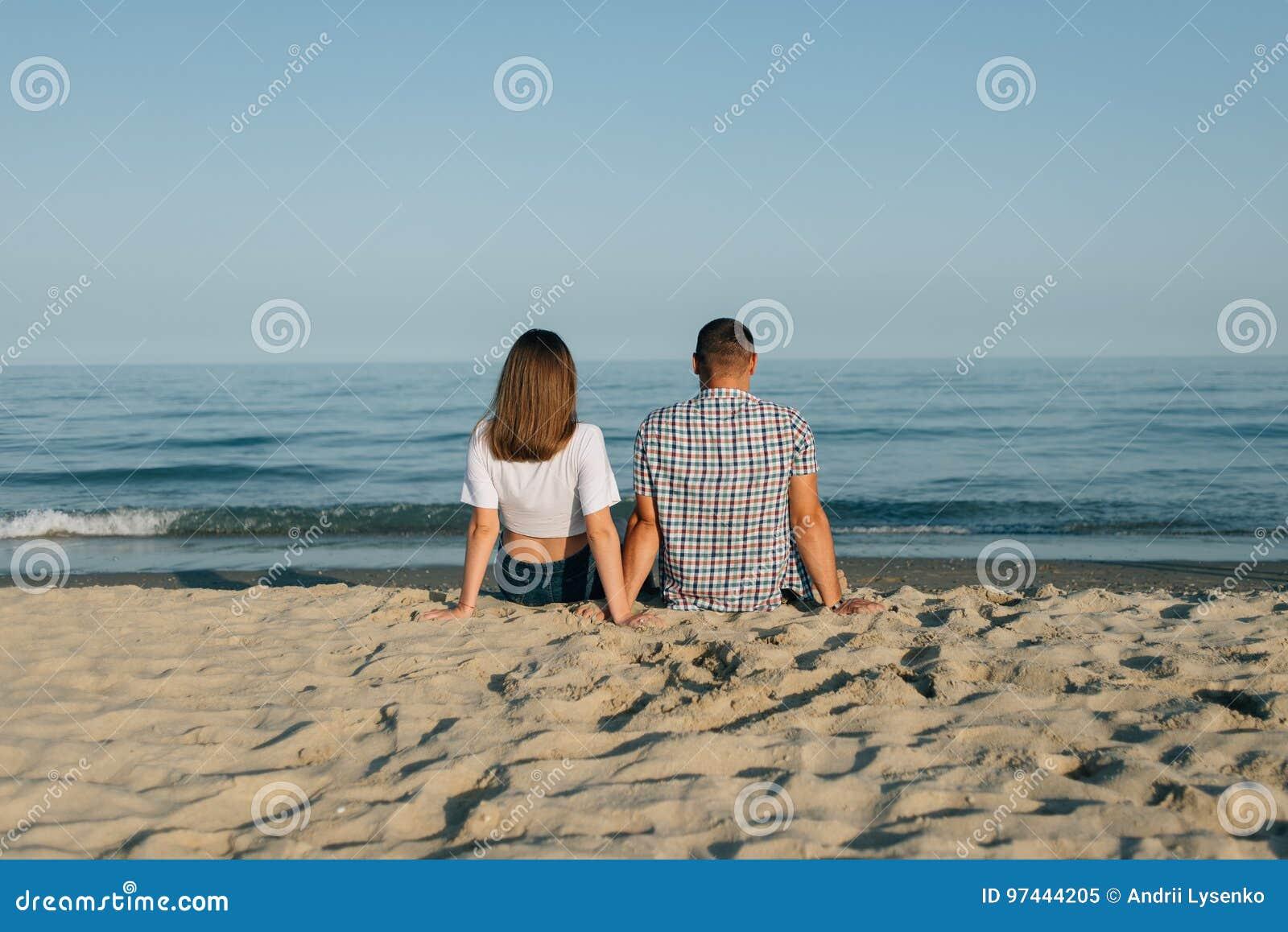 La coppia si siede sulla spiaggia, la retrovisione