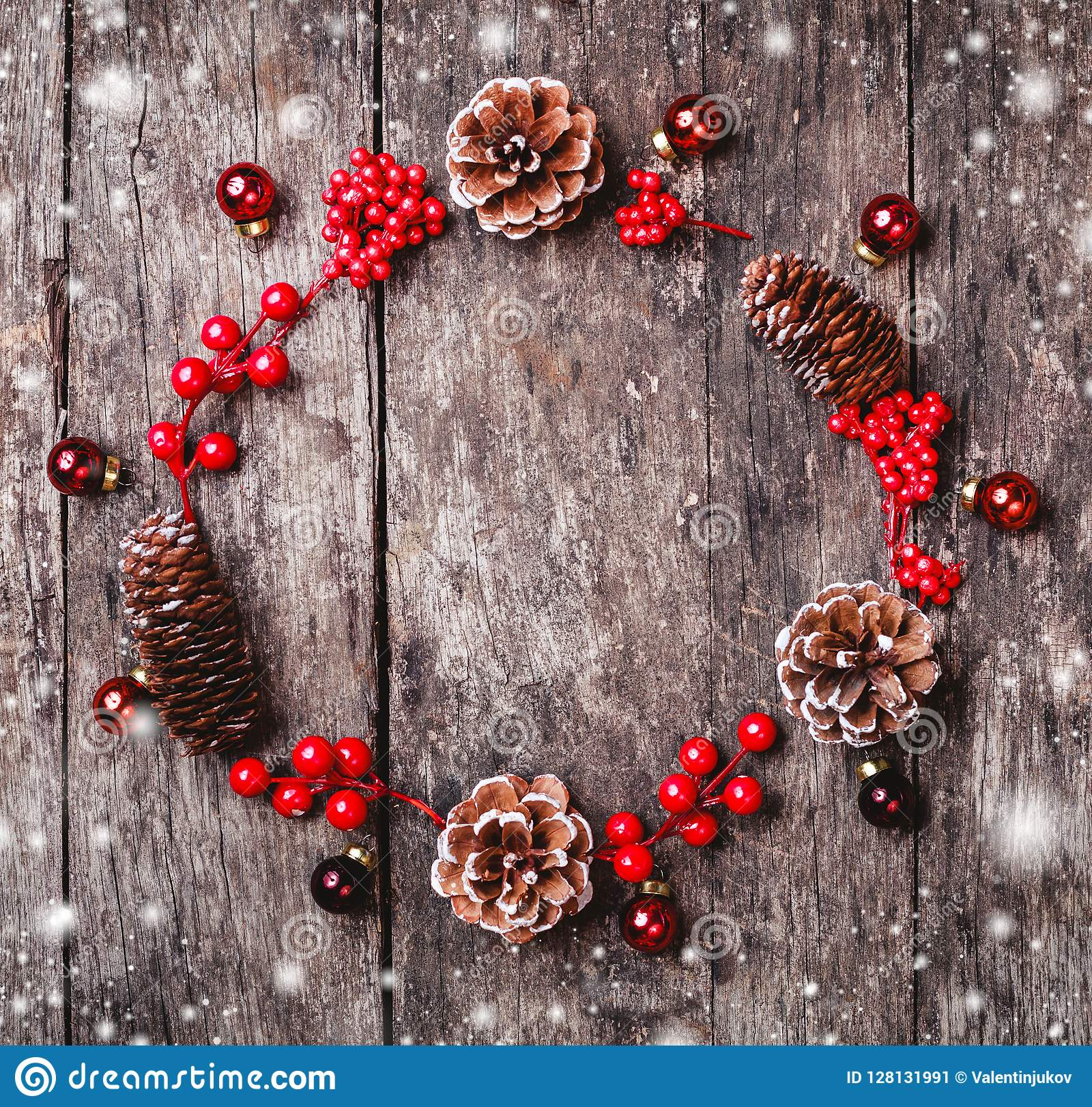 La corona di Natale di abete si ramifica, coni, decorazioni rosse su fondo di legno scuro