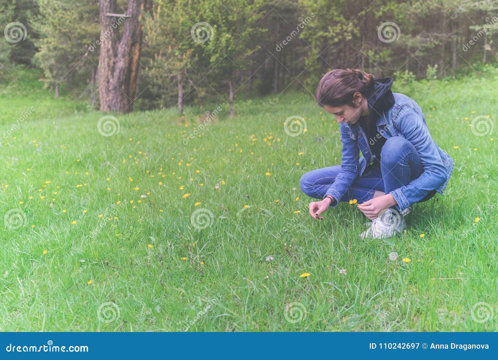 La cosecha adolescente hermosa de la muchacha florece en el prado