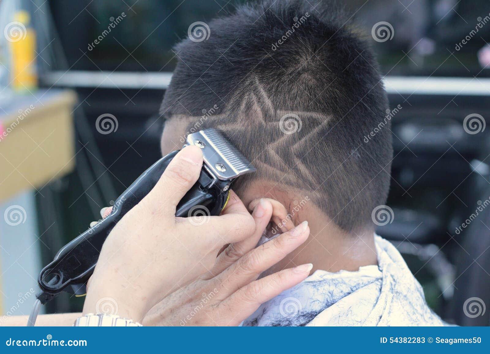 La coupe de cheveux du gar on avec la tondeuse et le rasoir dans le salon de coiffure photo Coupe garcon tondeuse