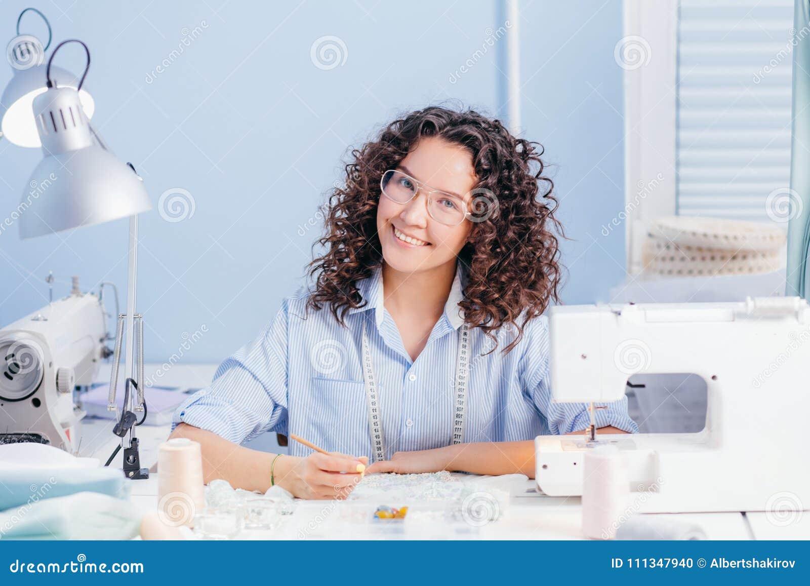 La couturière heureuse brodant avec la mode perle à l intérieur