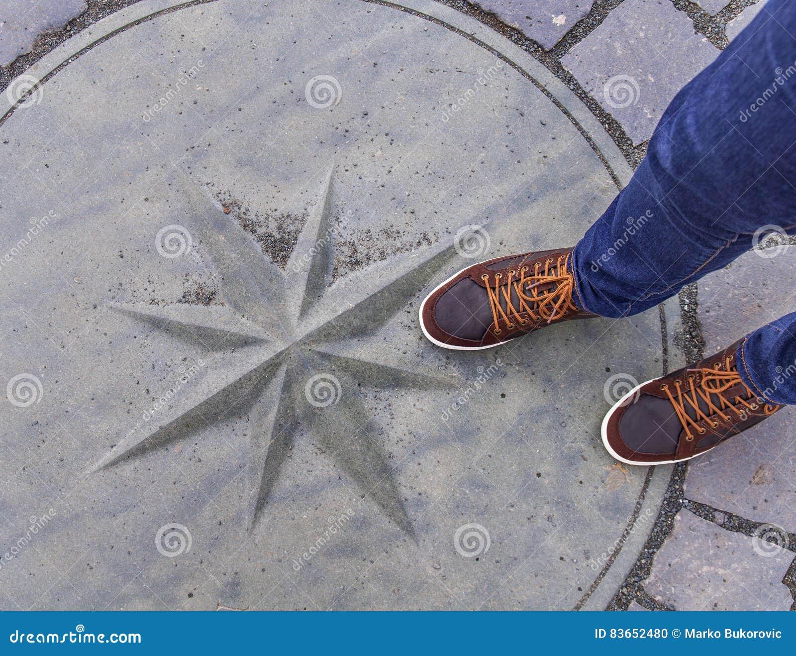 La couverture de drain de trou d homme sur des rues avec homme des pieds là-dessus