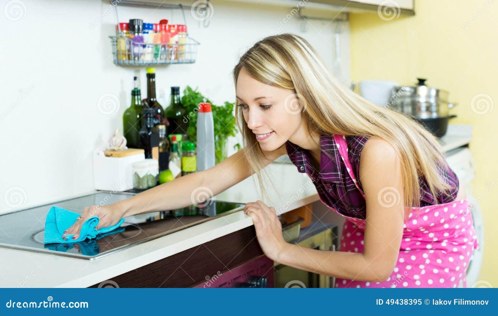 La criada limpia la estufa moderna