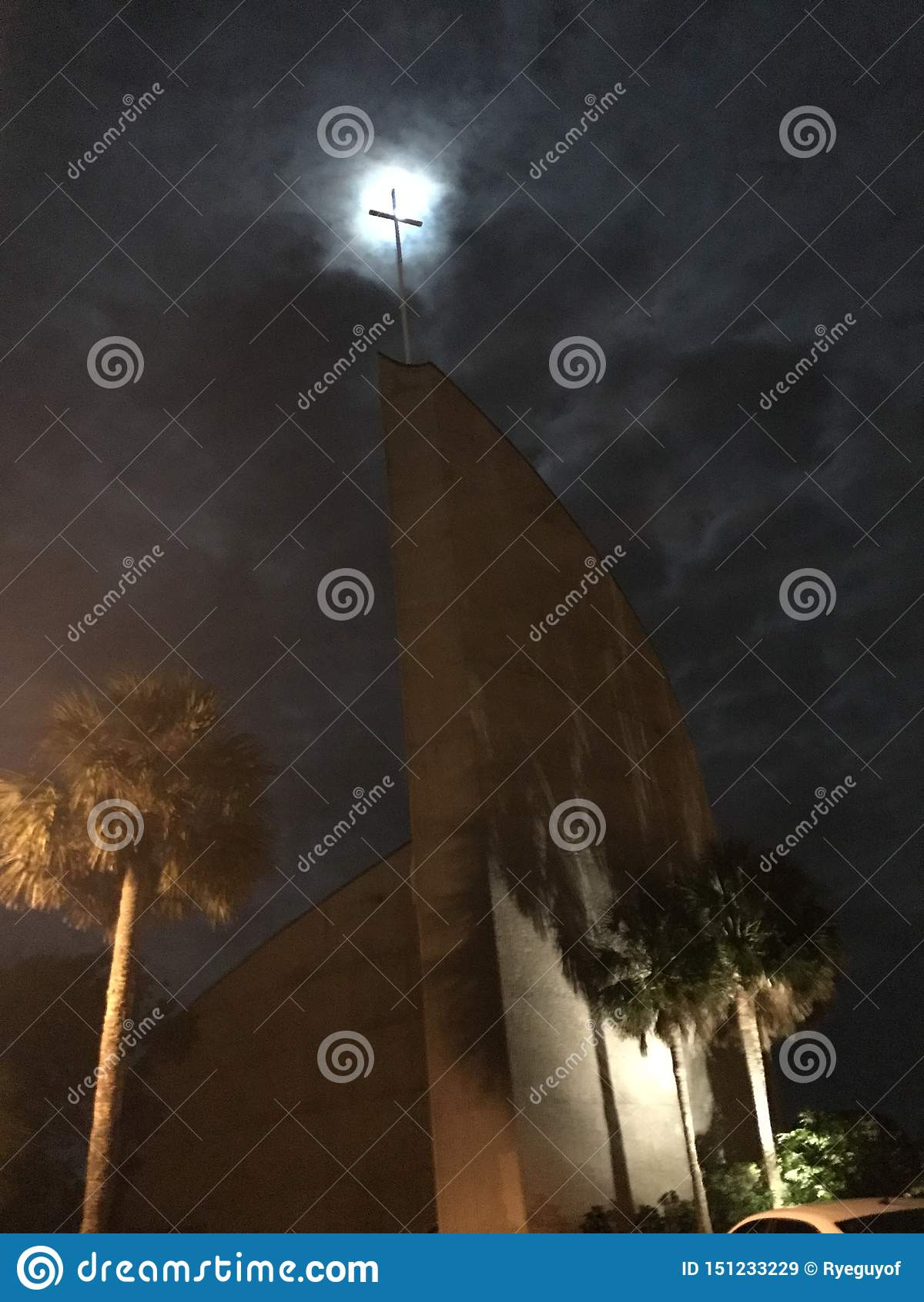 La cruz de la iglesia aparece encenderse para arriba mientras que la Luna Llena se muestra más allá de las nubes