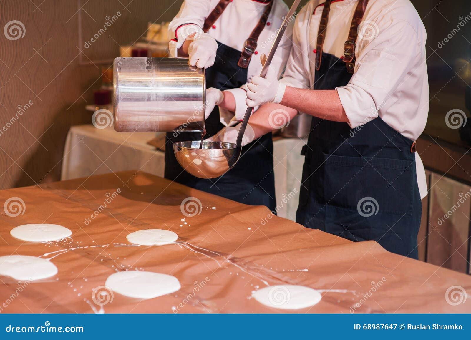 La cucharón del cocinero vierte las crepes grandes en la tabla