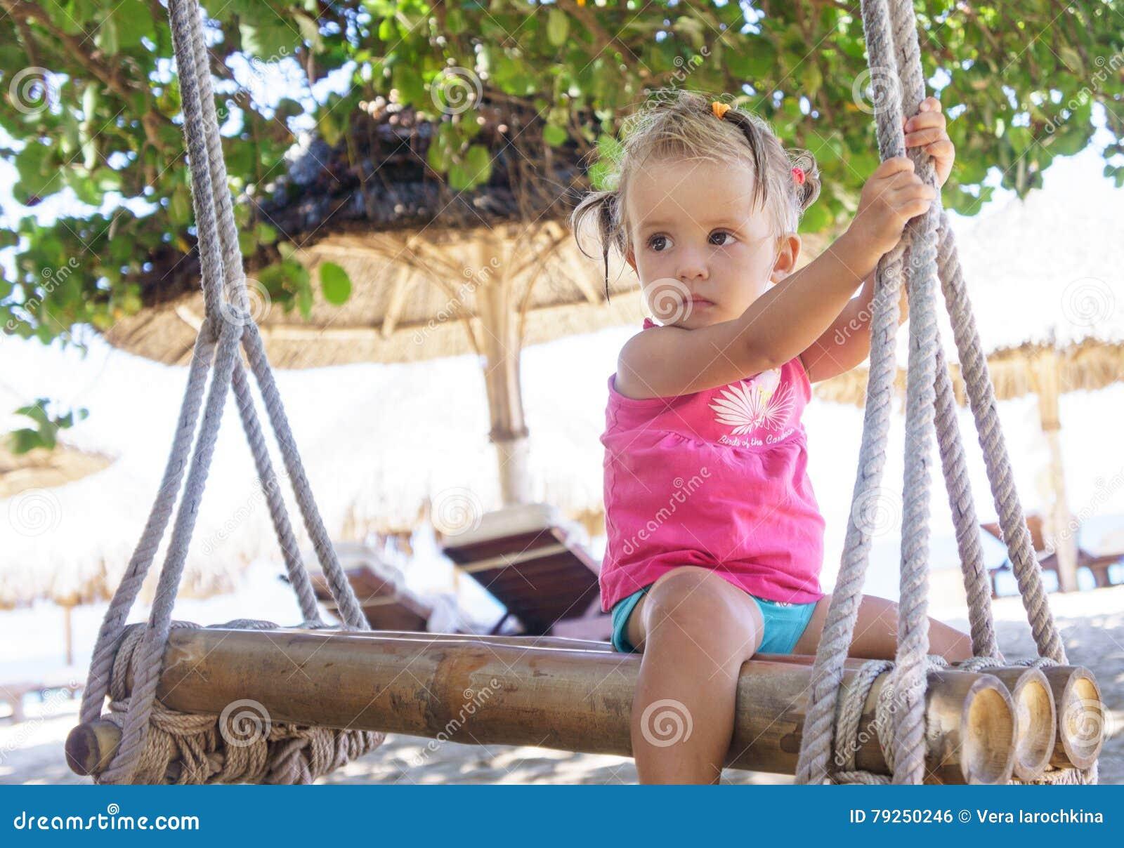 La cuerda que se sienta de la niña hermosa balancea en la playa